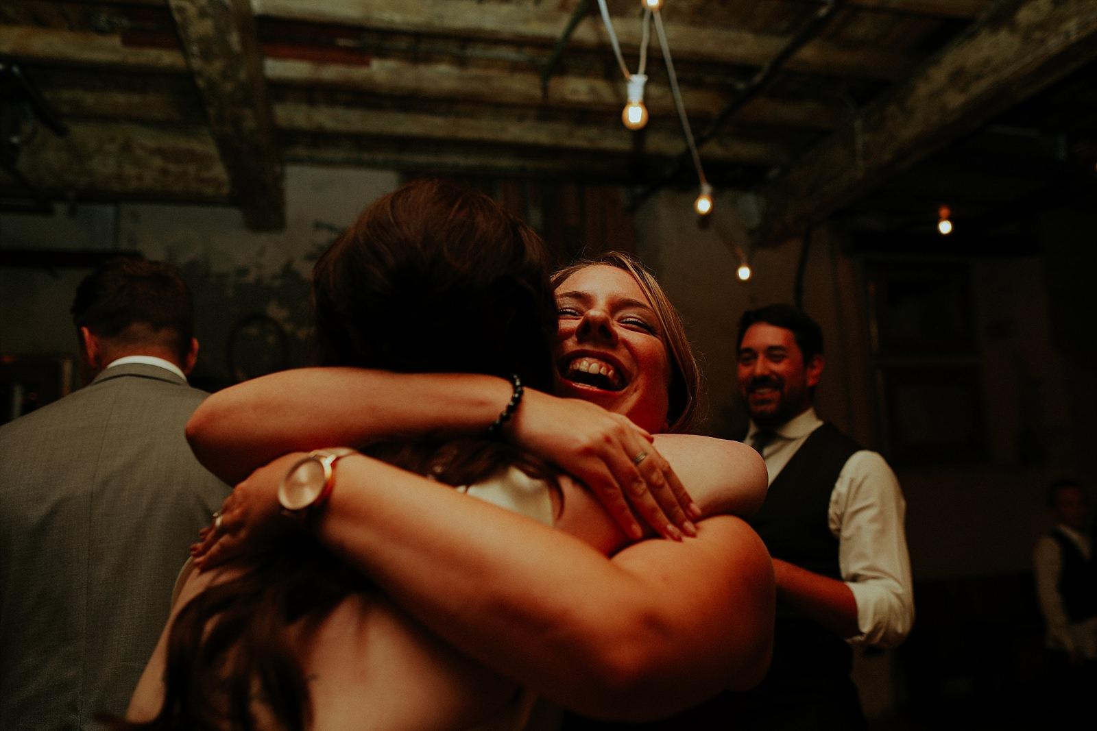 dancing wedding guests hug on the dance floor