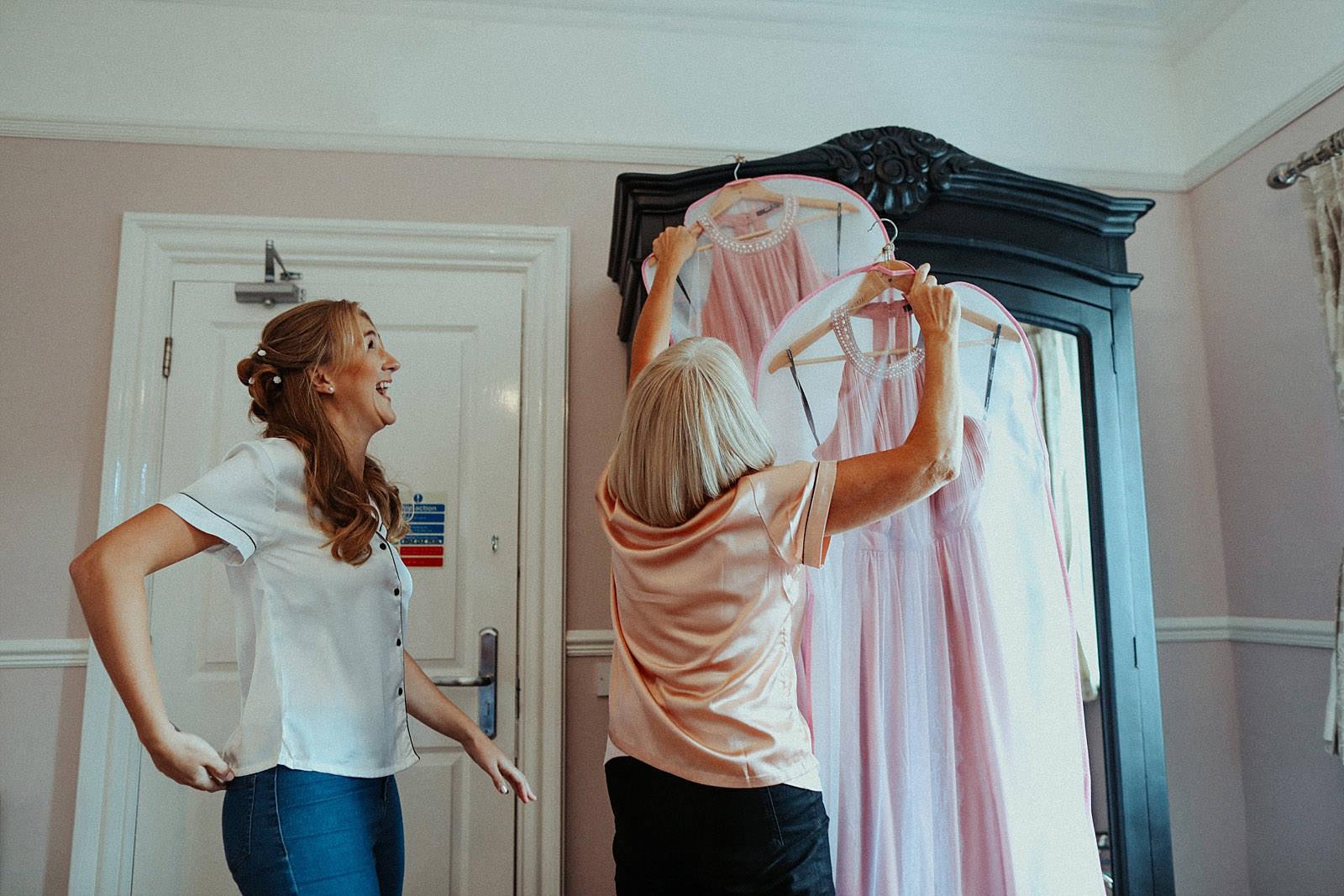 brides mum hooking dress on wardrobe