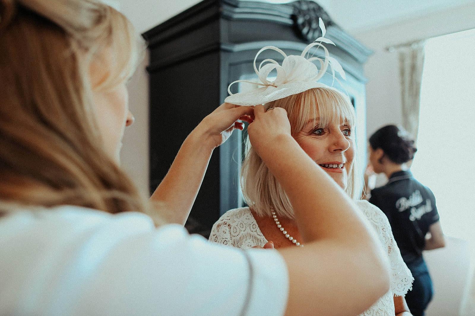 bride fixing mums fascinator