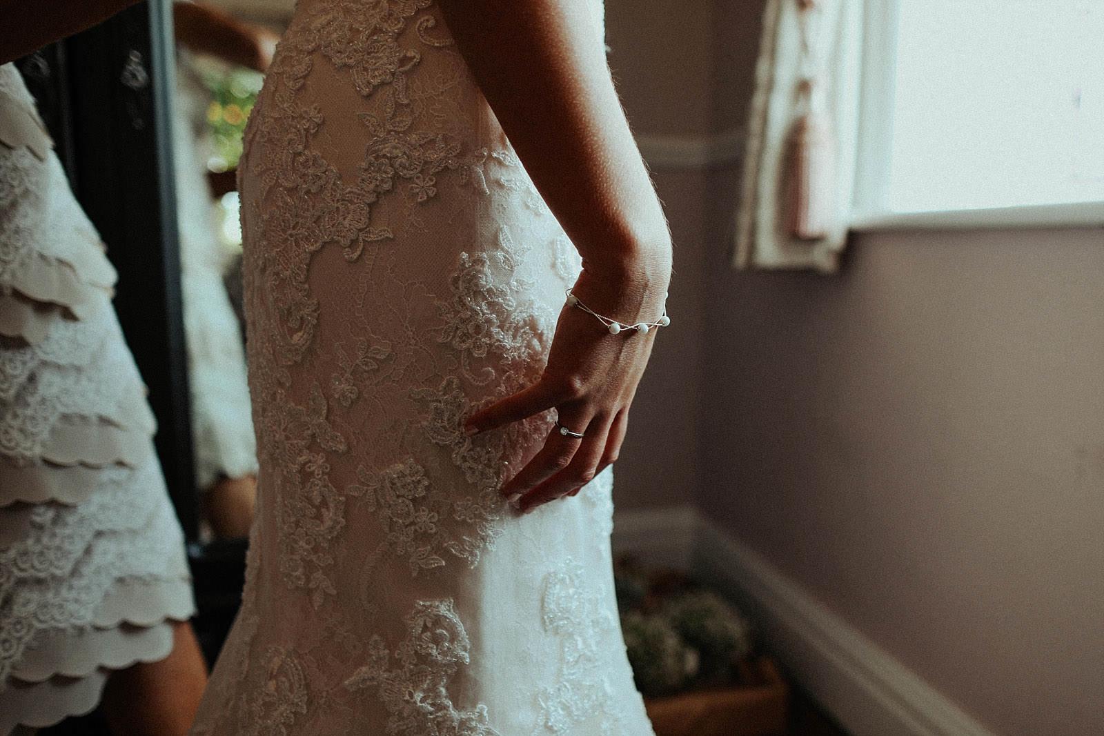 brides hands close to wedding dress