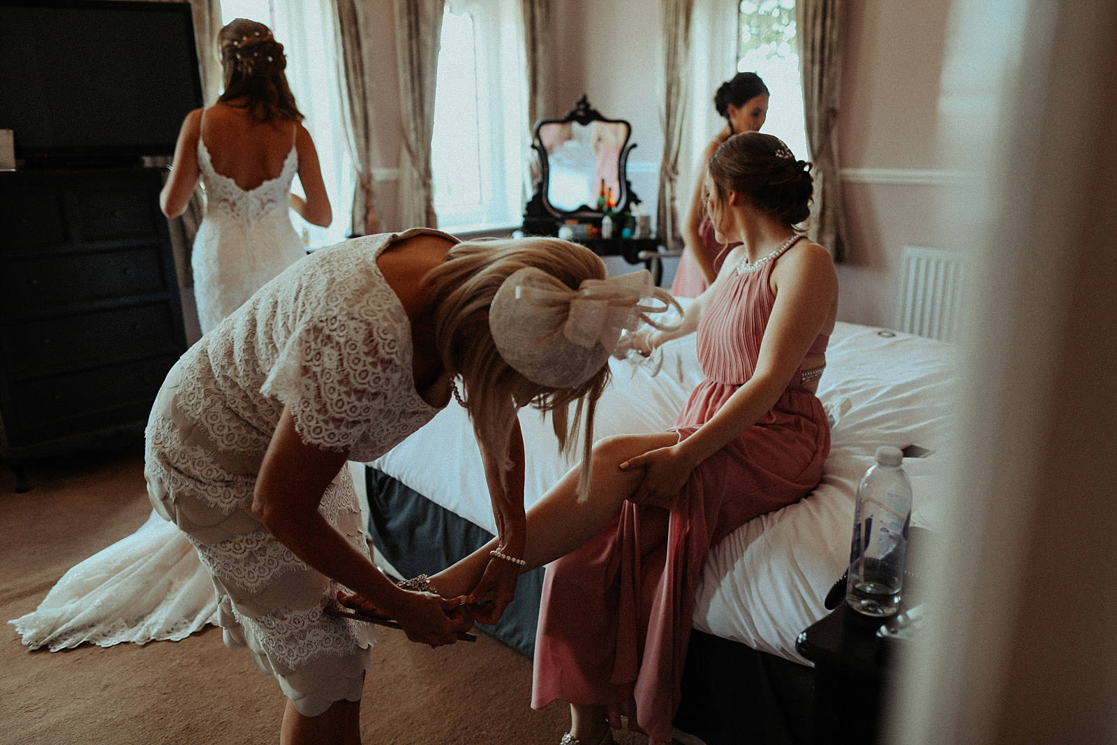 mother of the bride help bridesmaid out her shoes on