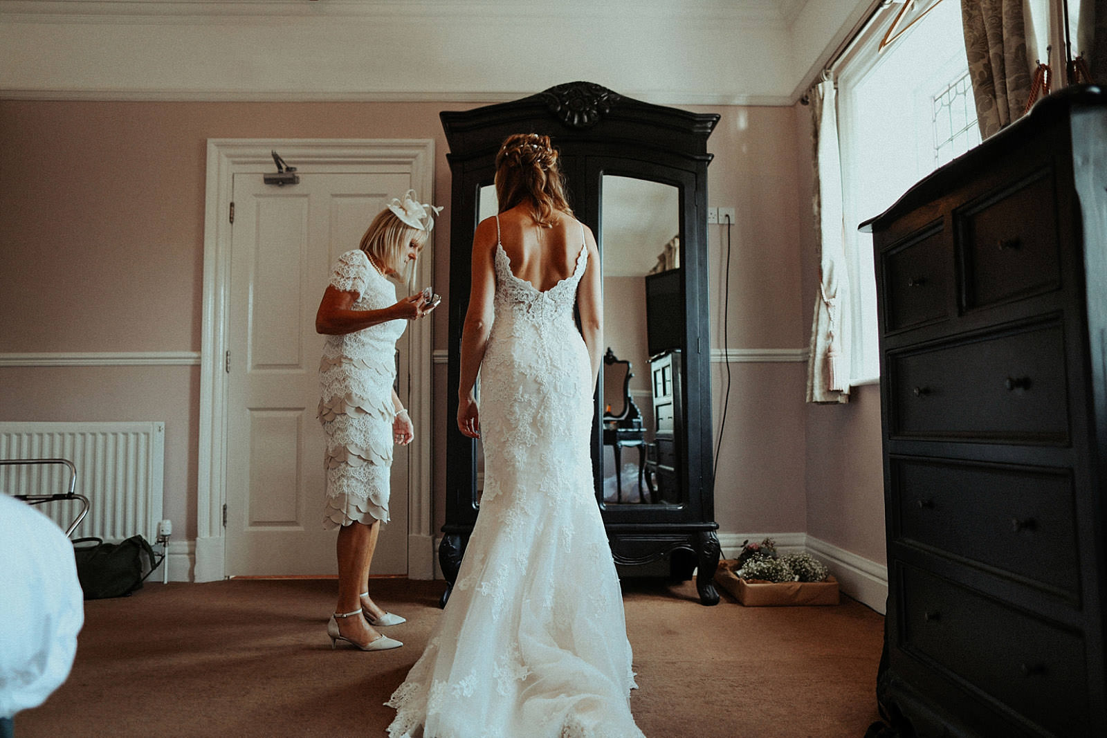 bride standing and looking at her self in her wedding dress
