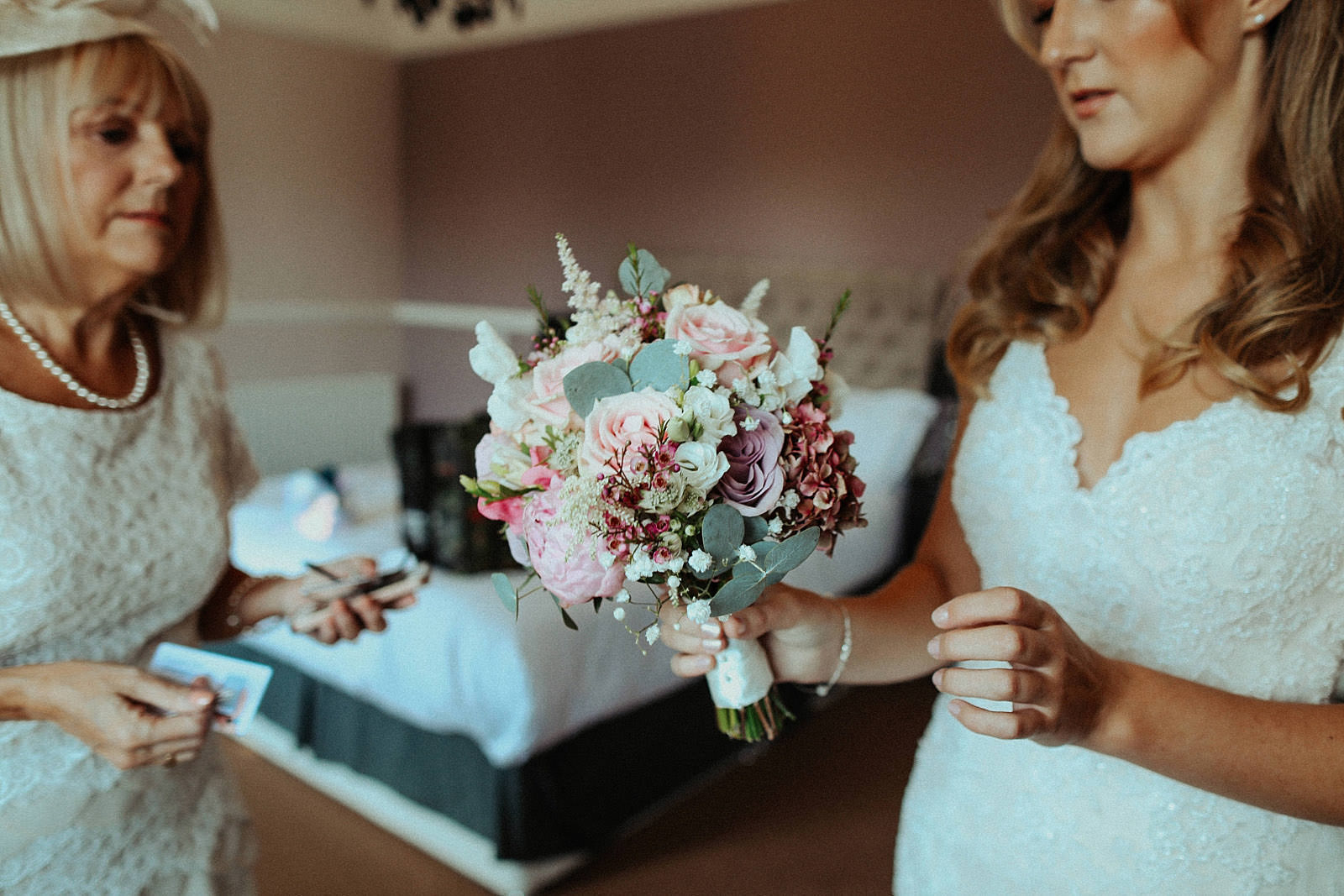 Bride holding her flowers whilst getting ready at the royal oak in cheshire