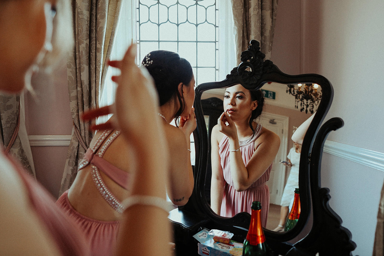 bridesmaid putting on her lipstick in a mirror