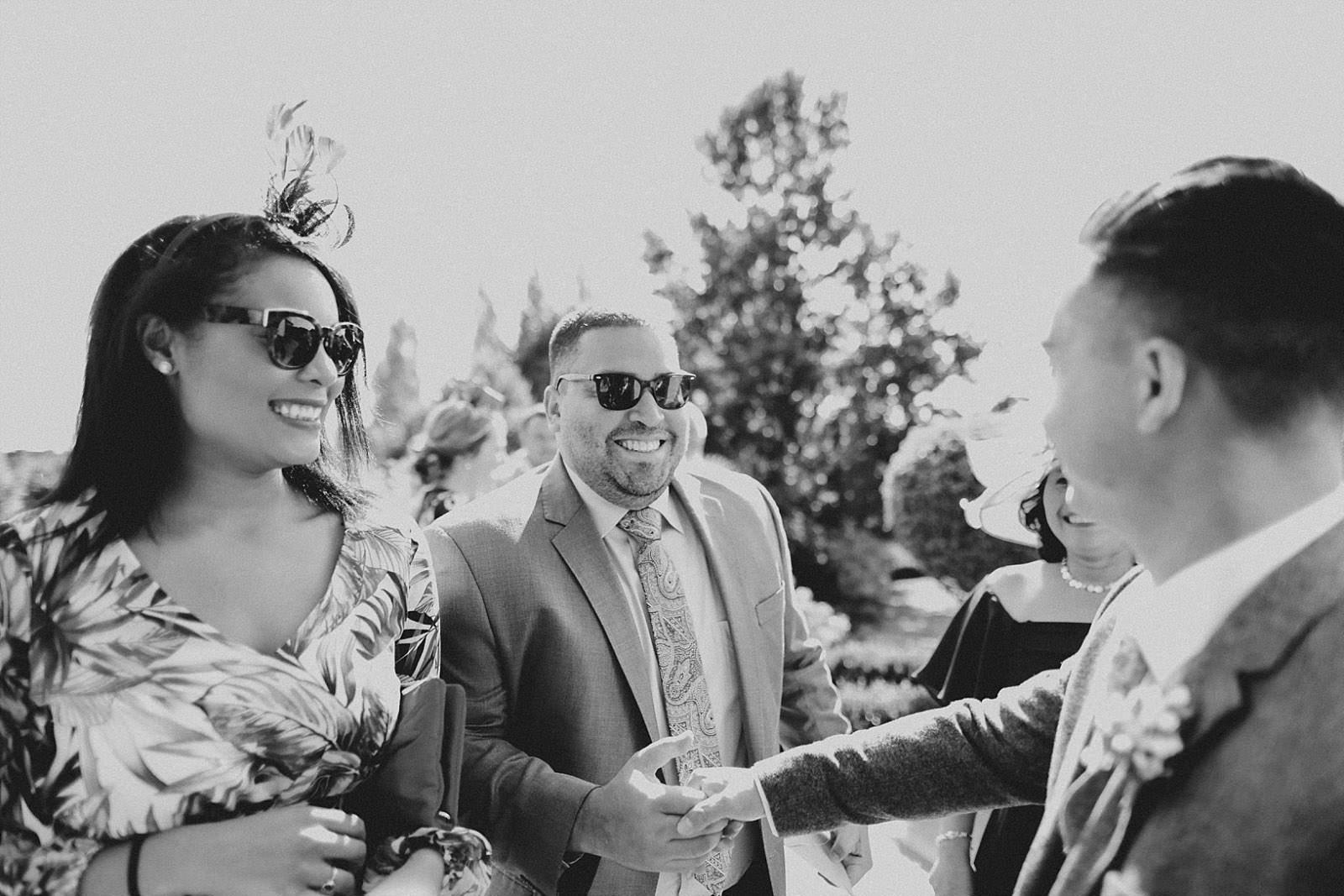 groom greeting guests at wedding venue