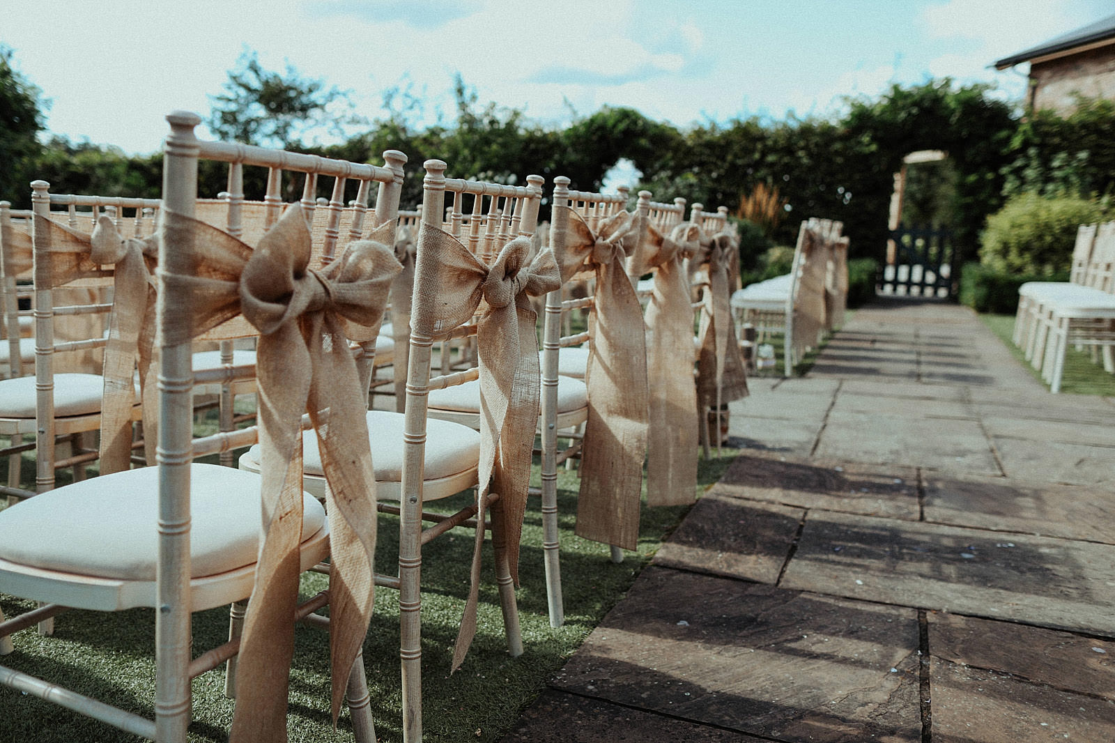 hessian bows on chairs at an outdoor wedding ceremony
