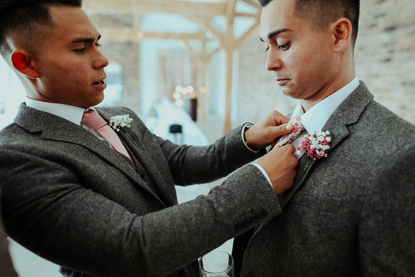 best man fixes grooms button hole flower