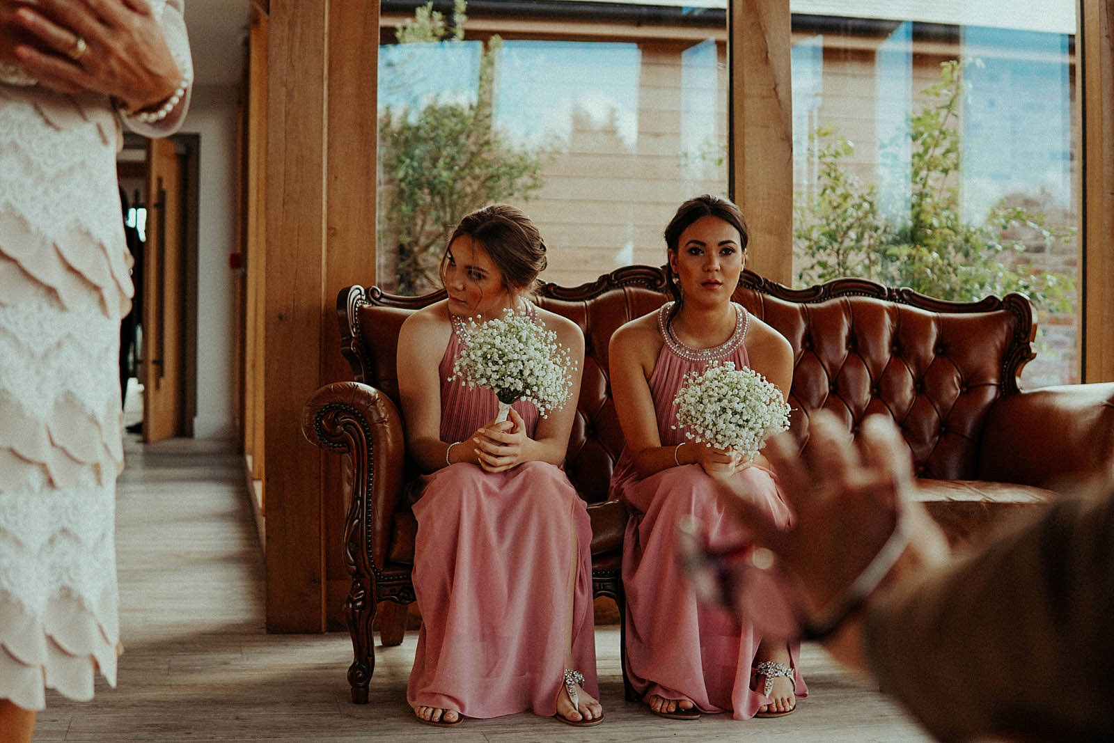 two bridesmaids waiting on a chair