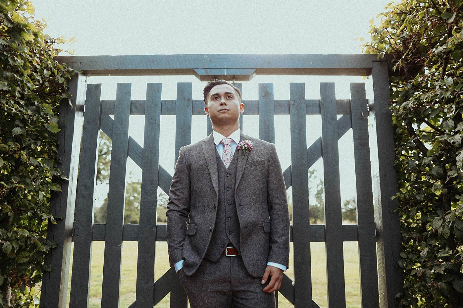 groom standing in suit with fence behind him