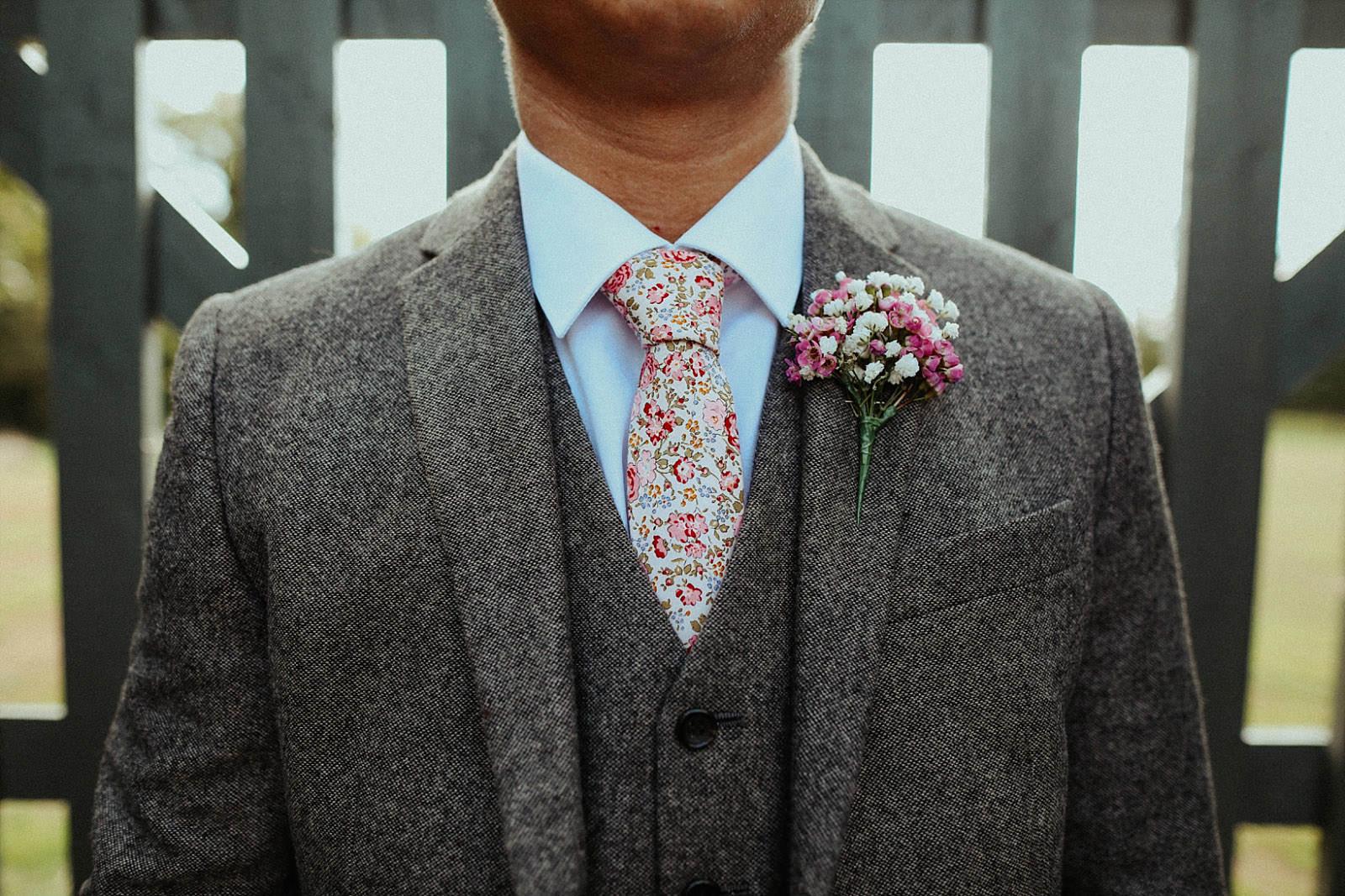 flowery grooms tie and pocket square on tweed suit