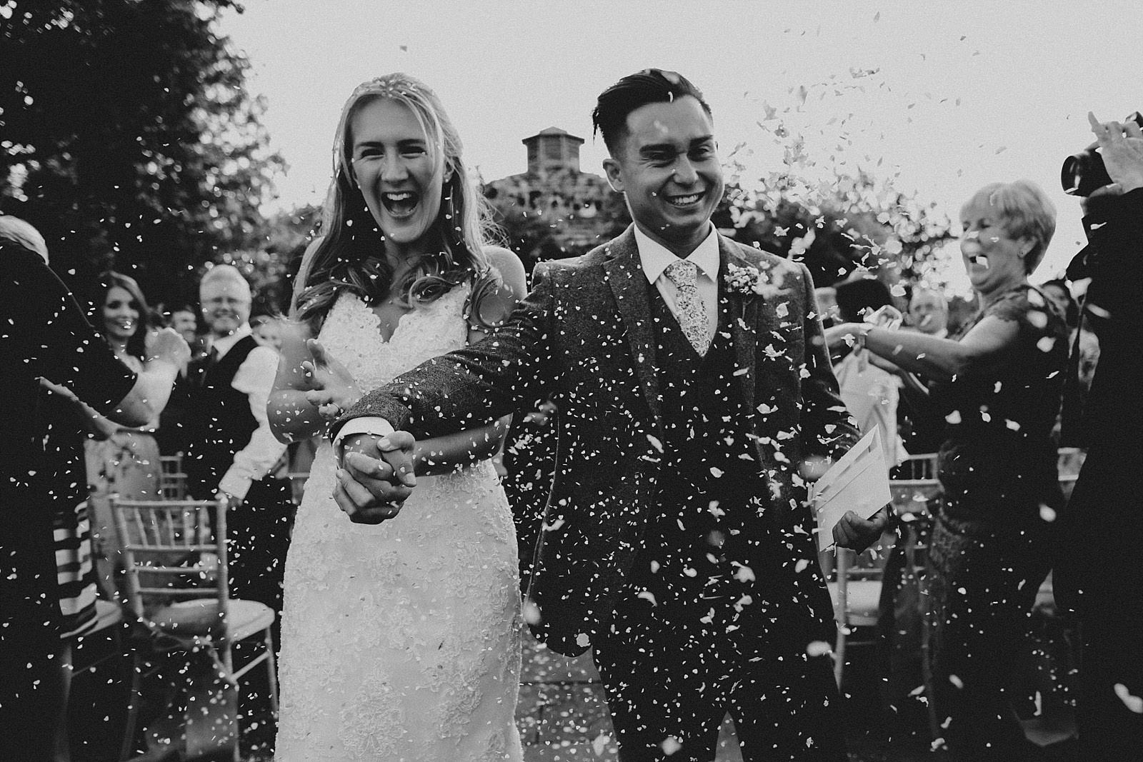 bride and groom get confetti thrown on them