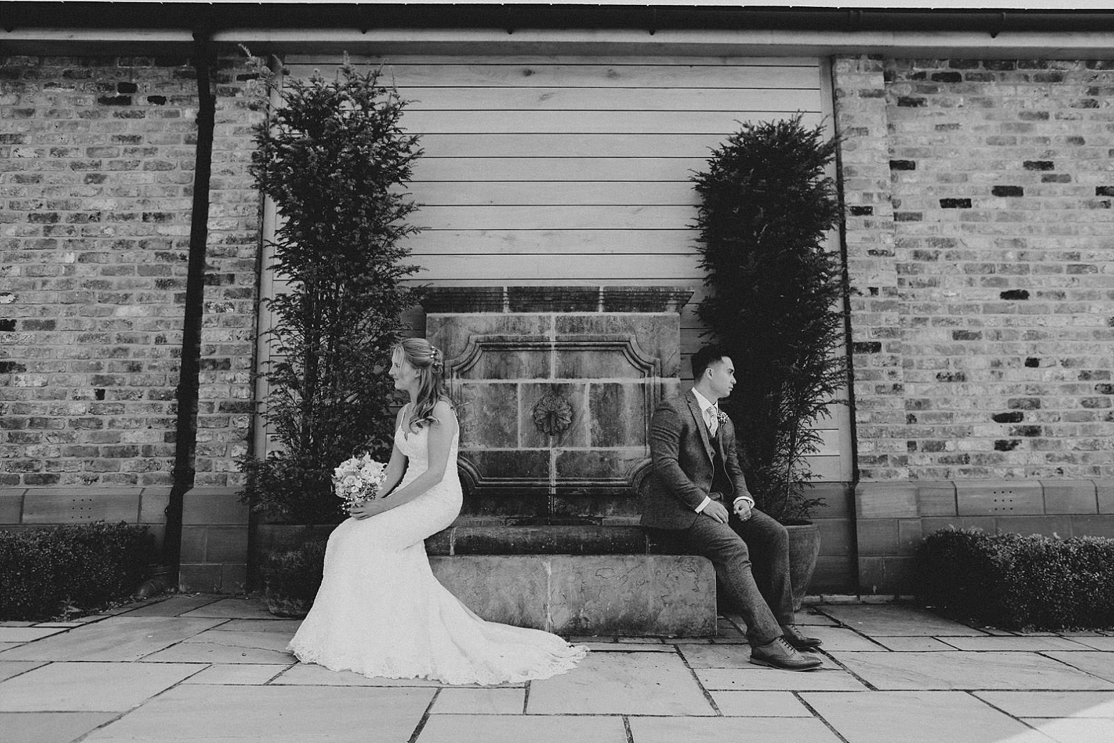 bride and groom sat on a fountain