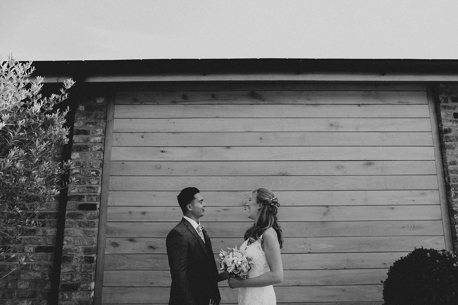 bride and groom infront of wood panel wall