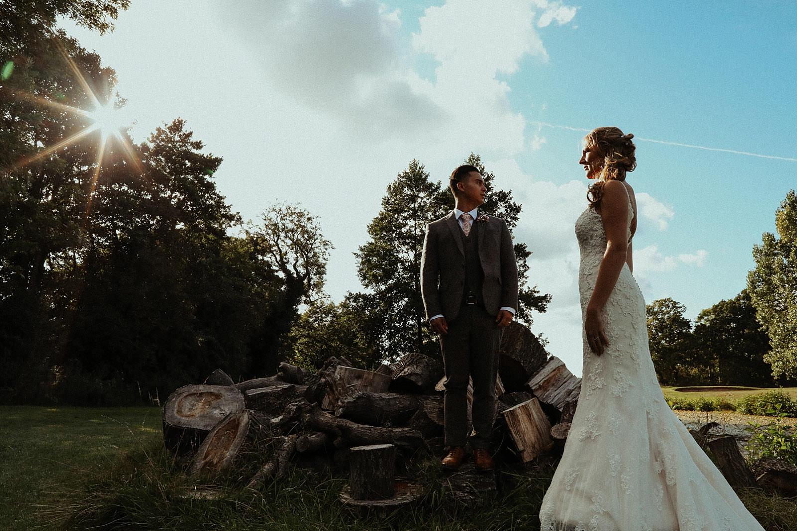 bide and groom pose on log pile