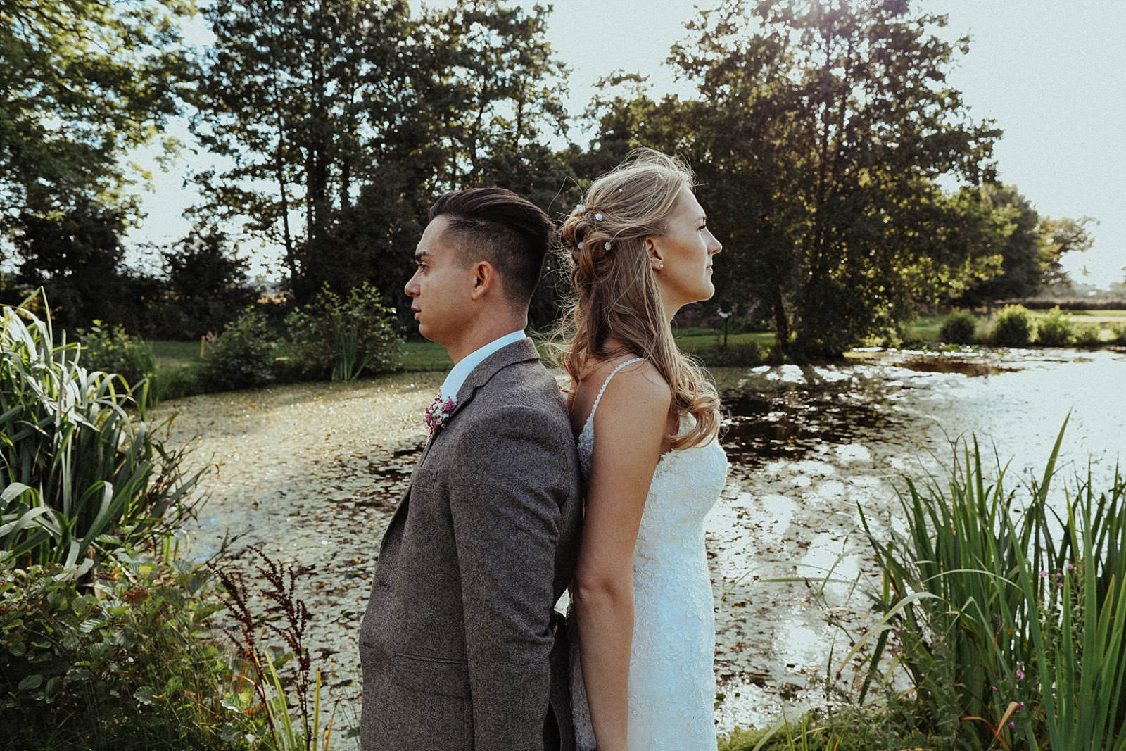 back to back bride and groom in front of lake with trees