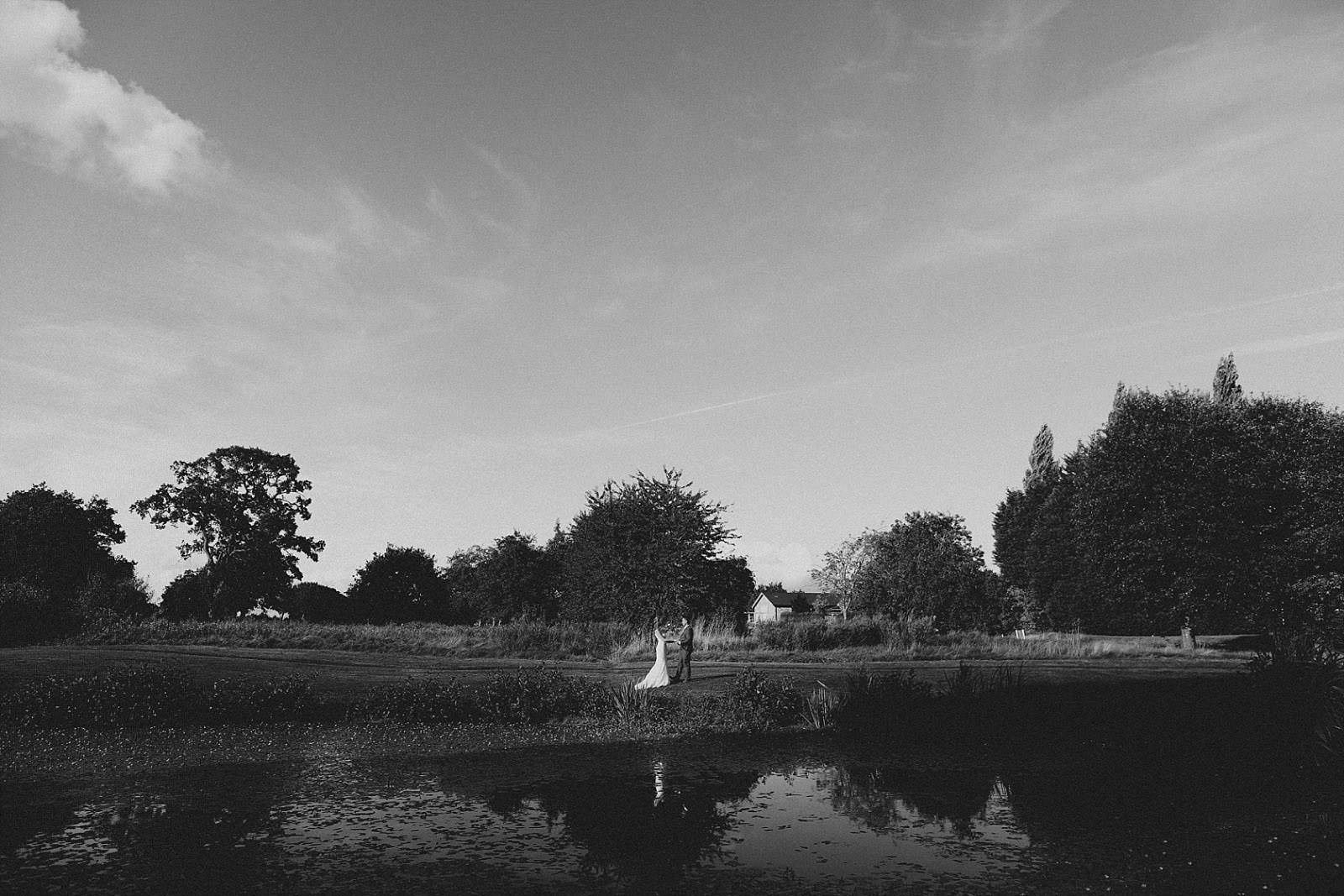 wide shot of wedding couple over a lake