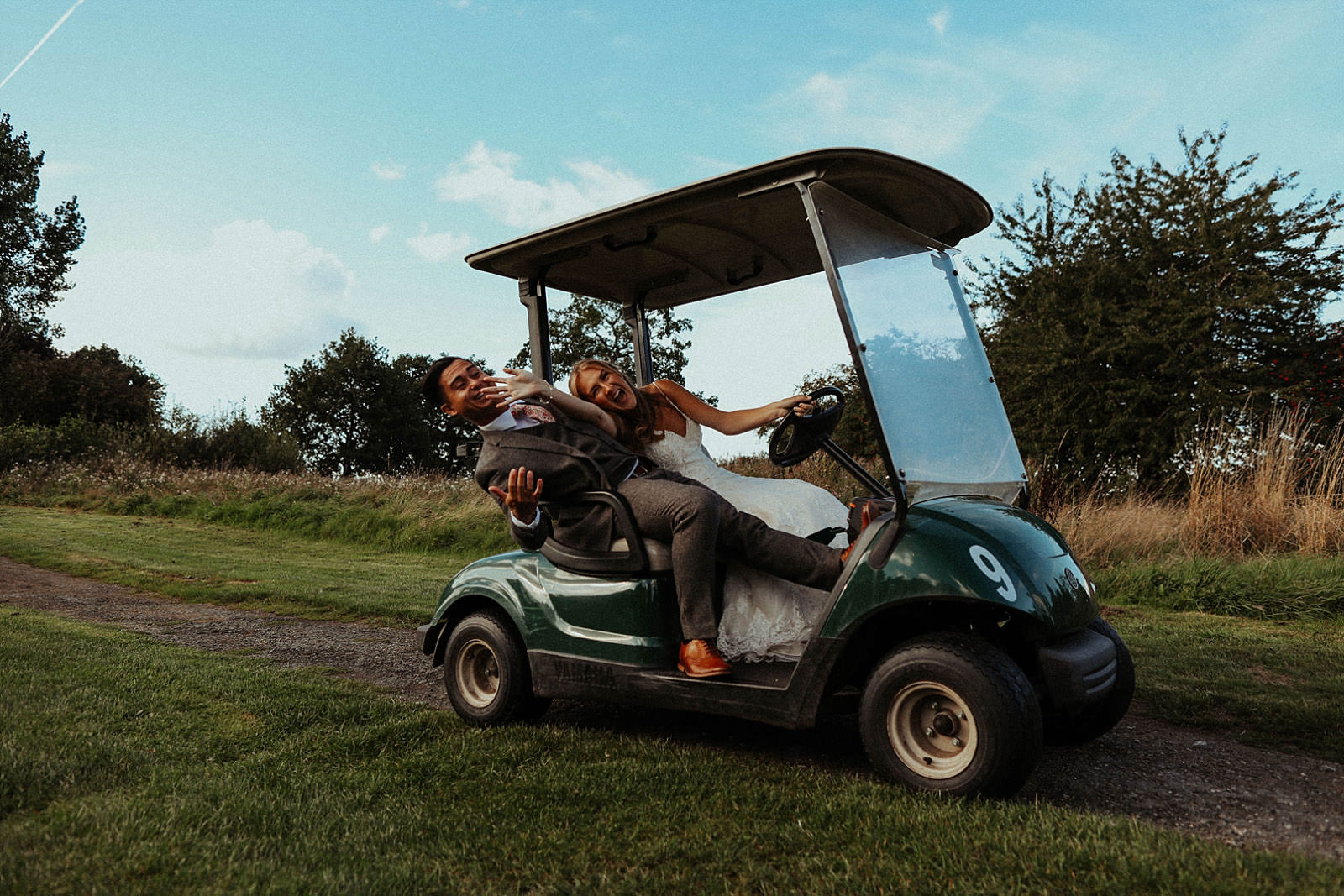 fun shot of newlyweds on a golf buggy at pryors hayes
