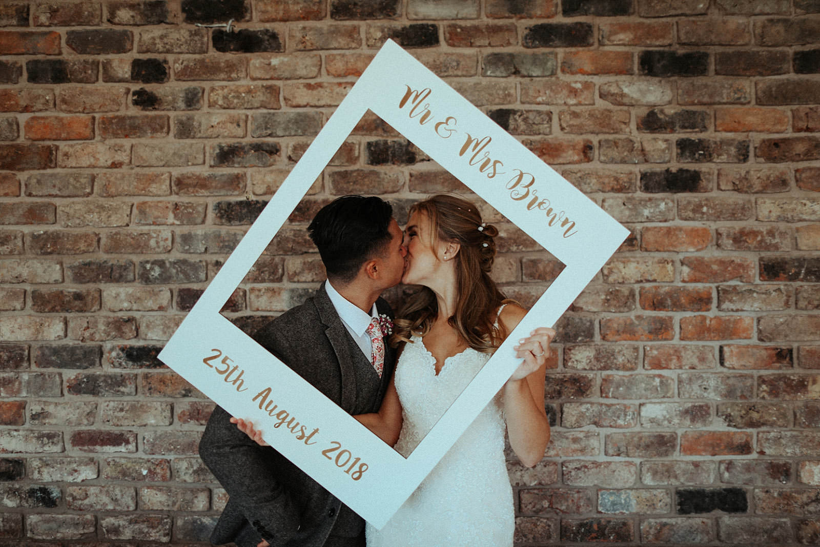 kissing bride and groom with sign