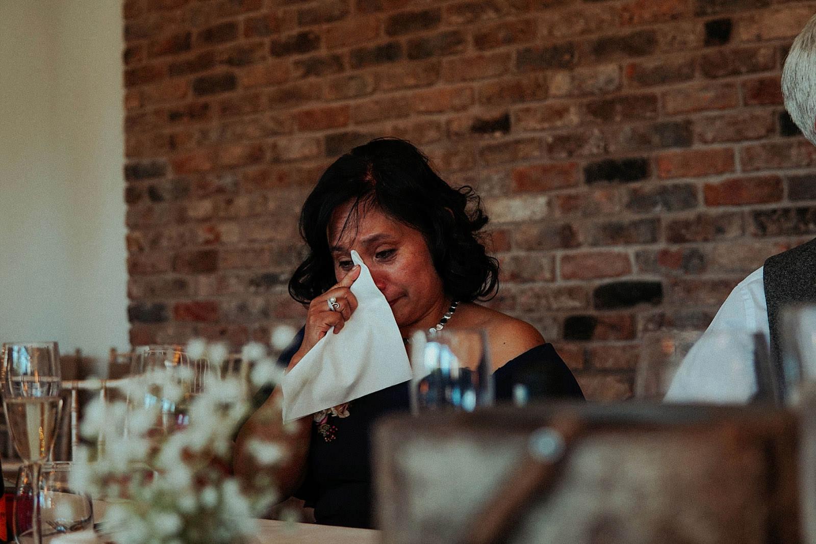 mum using napkin to wipe away tears