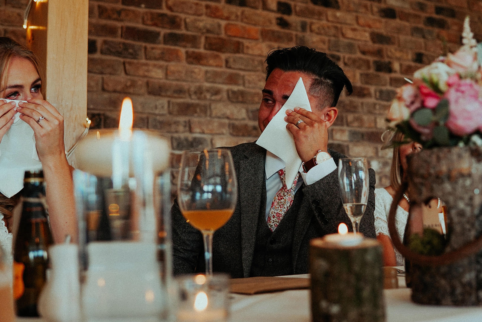 groom crying and using a napkin to wipe tears away