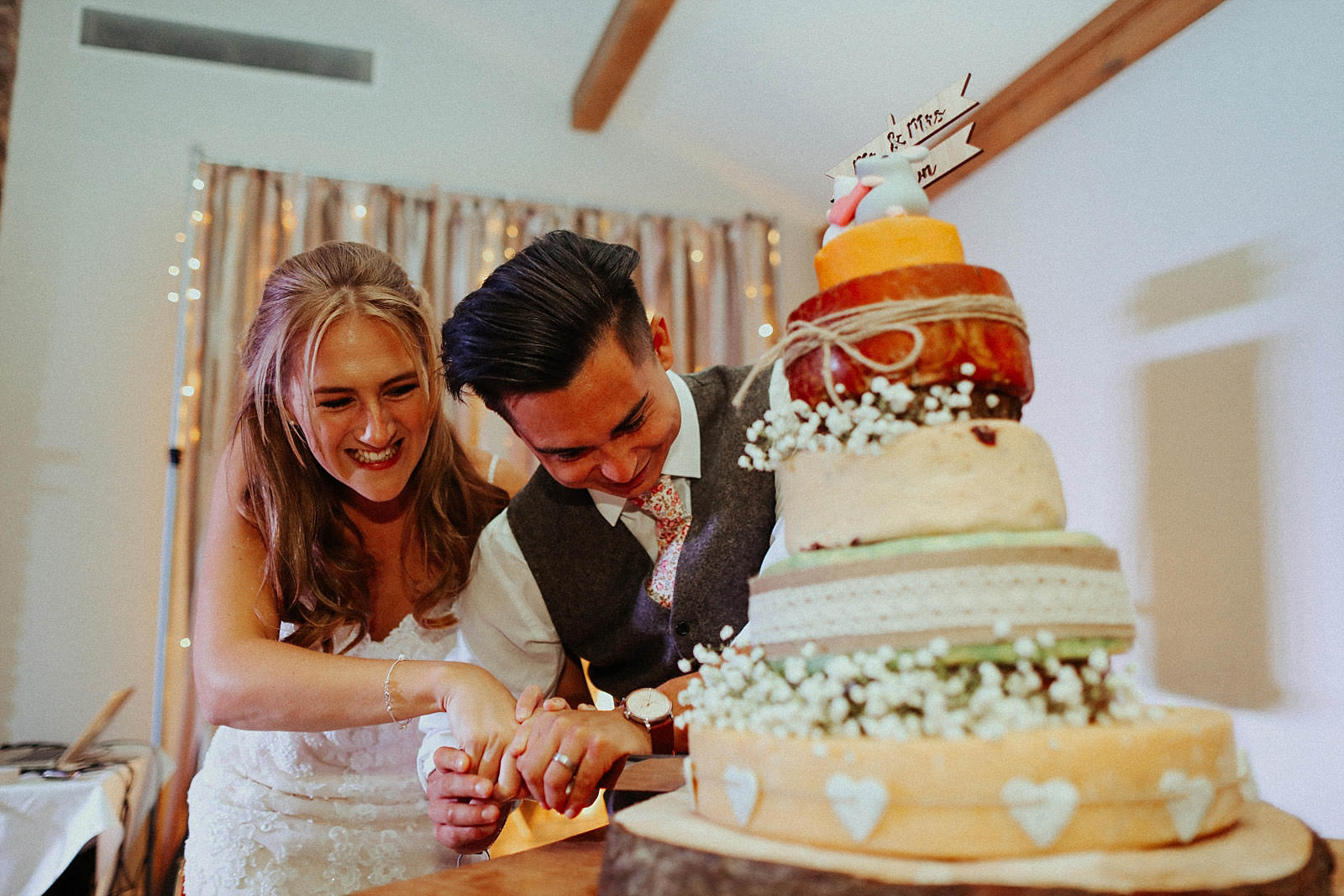 bride and groom find it hard to cut their wedding cake