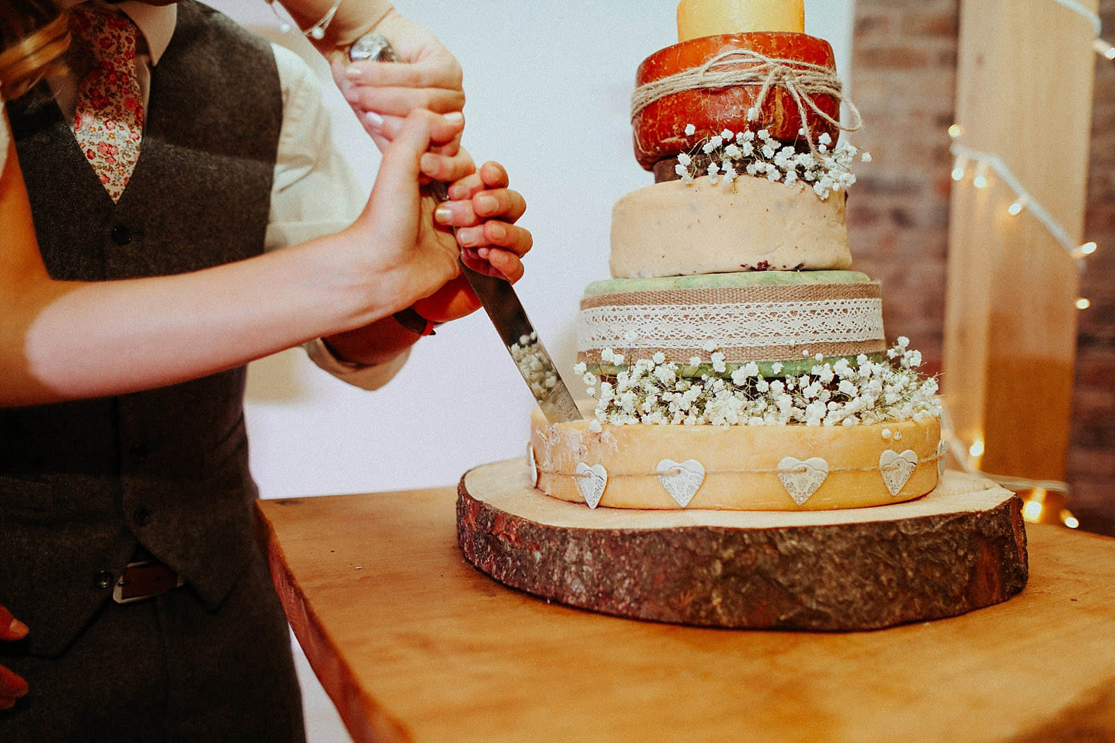 knife going in to a cheese wedding cake