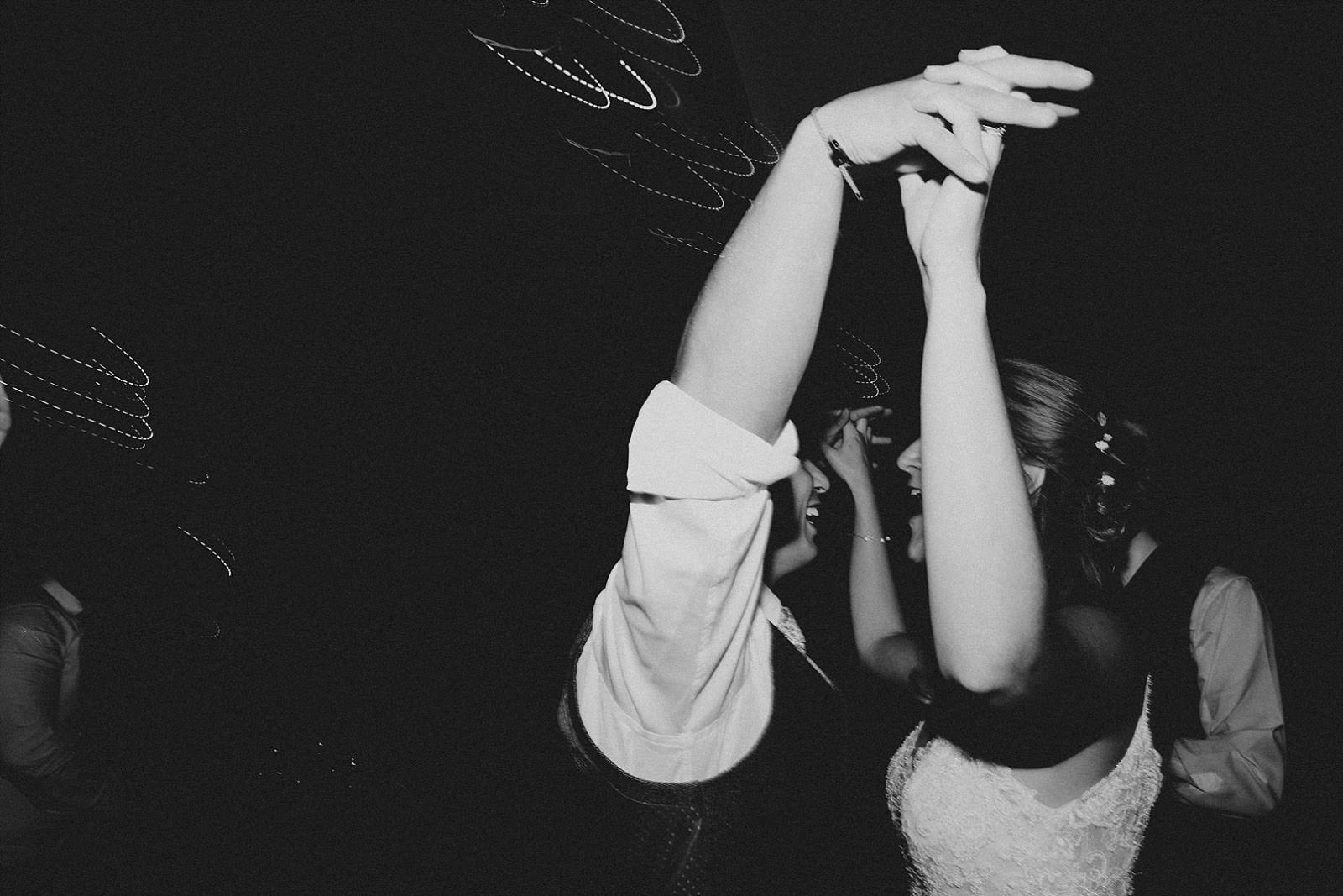 bride and groom with arms in the air whilst dancing