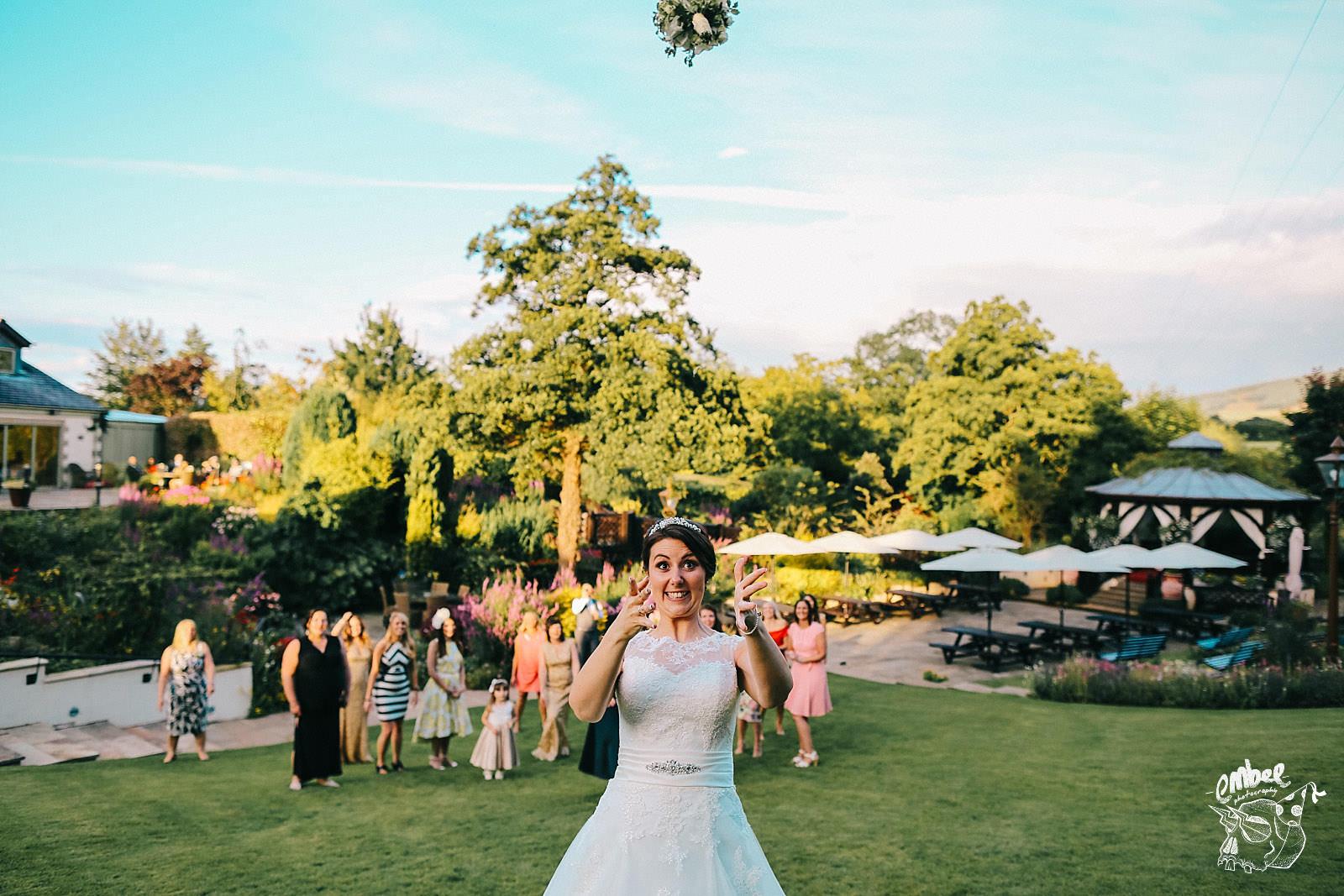 bride throws her wedding flower bouquet in the air