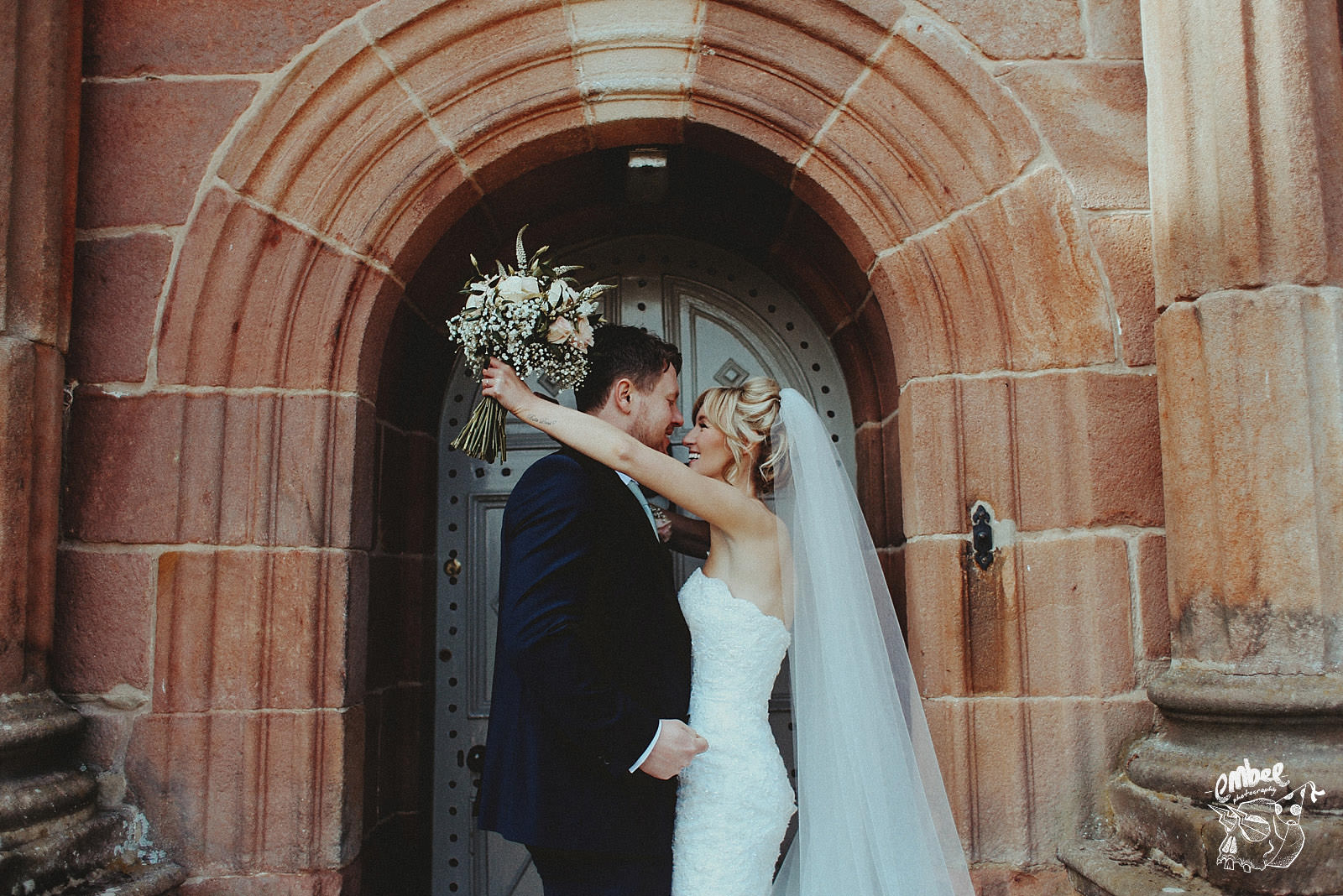 natural shot of bride wrapping her arms around her husband
