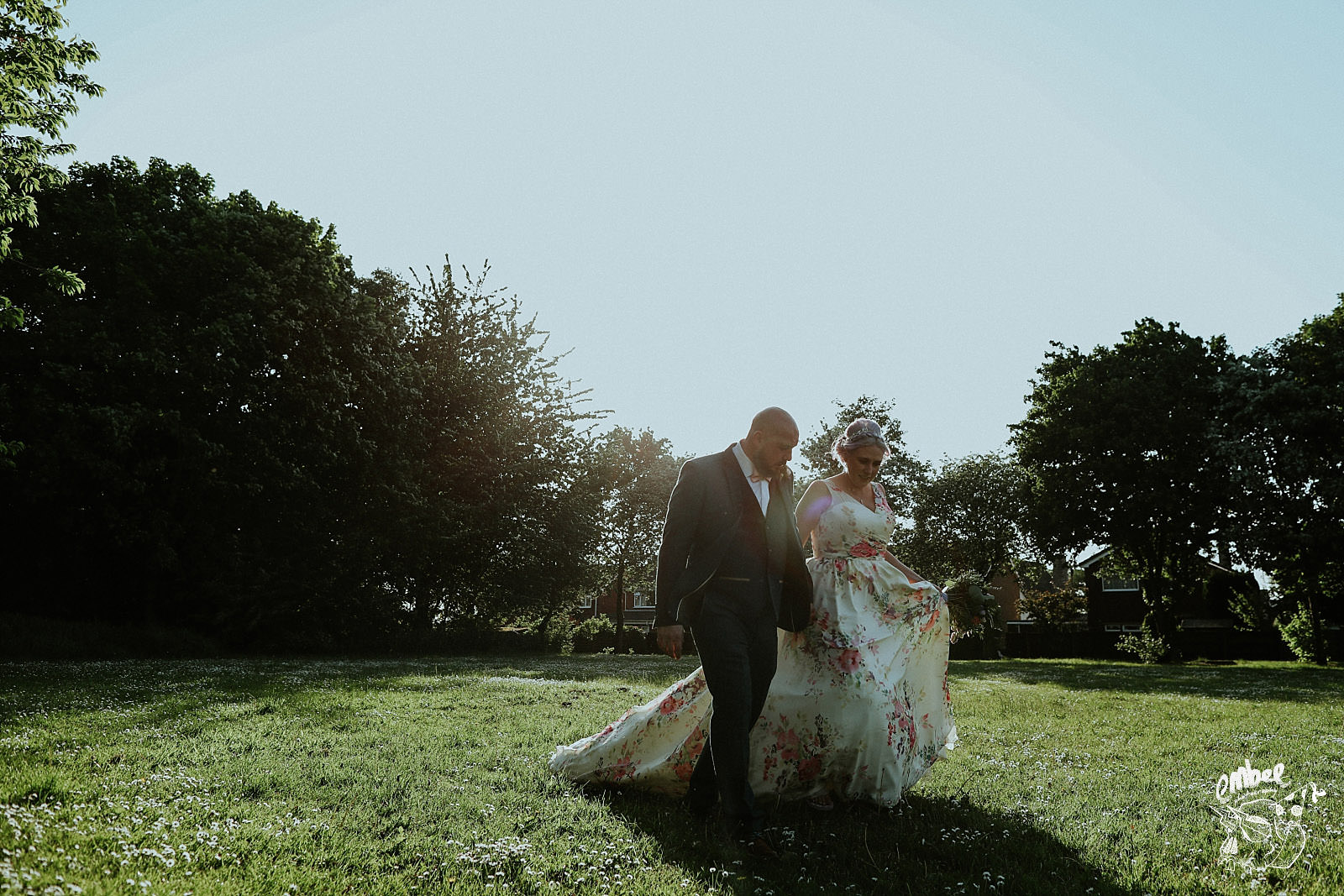 brides wearing flowery dress walking through a field with her husband