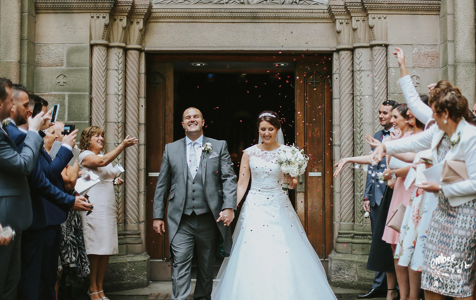 confetti being thrown over bride and groom at a church by guests