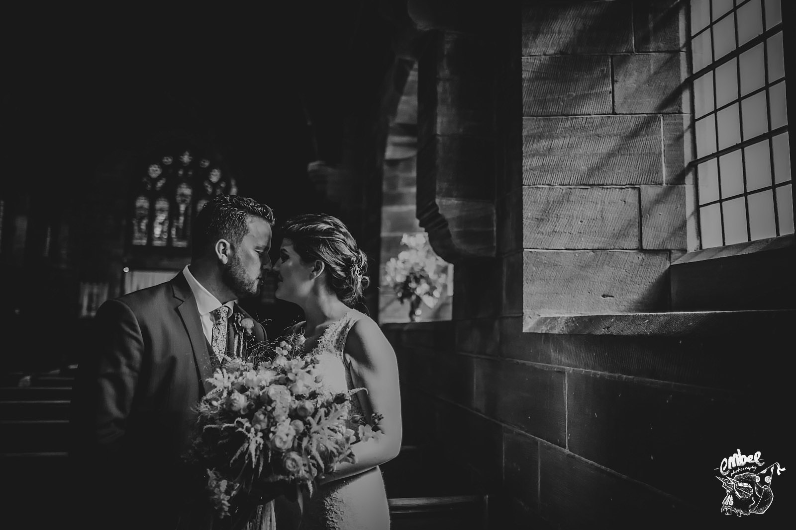 bride and groom in a church with window light pouring in