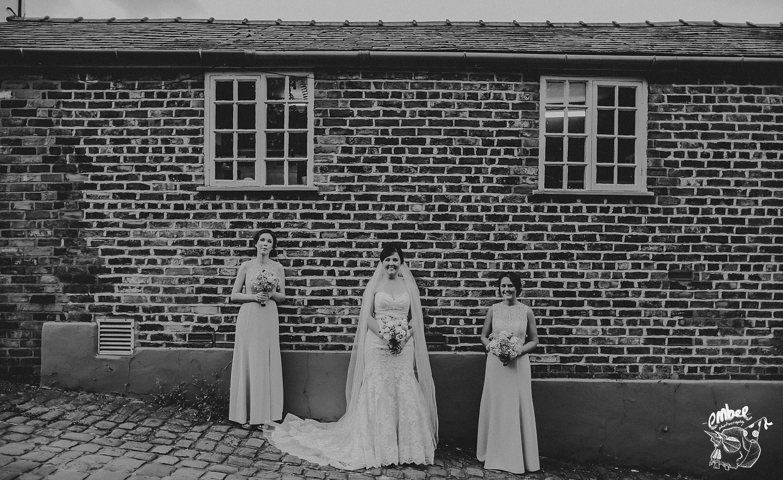 bride and bridesmaids against a windowed building