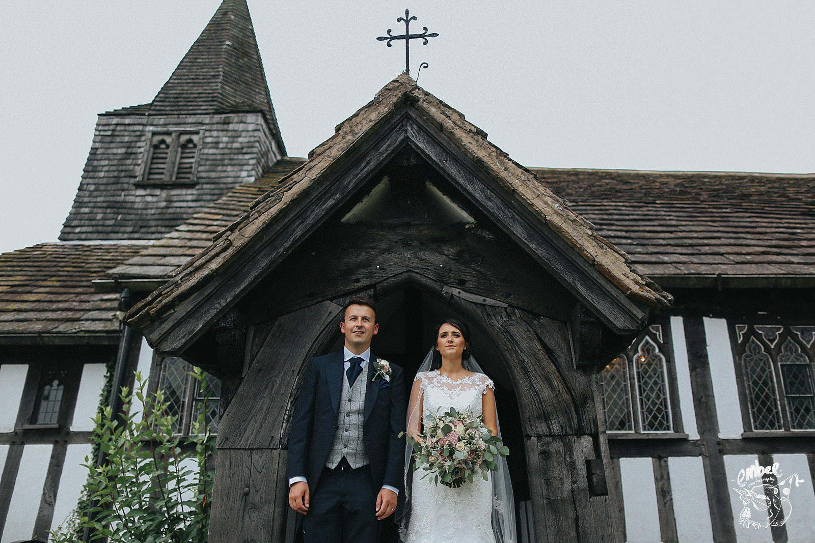 bride and groom infront of tudor style church in cheshire