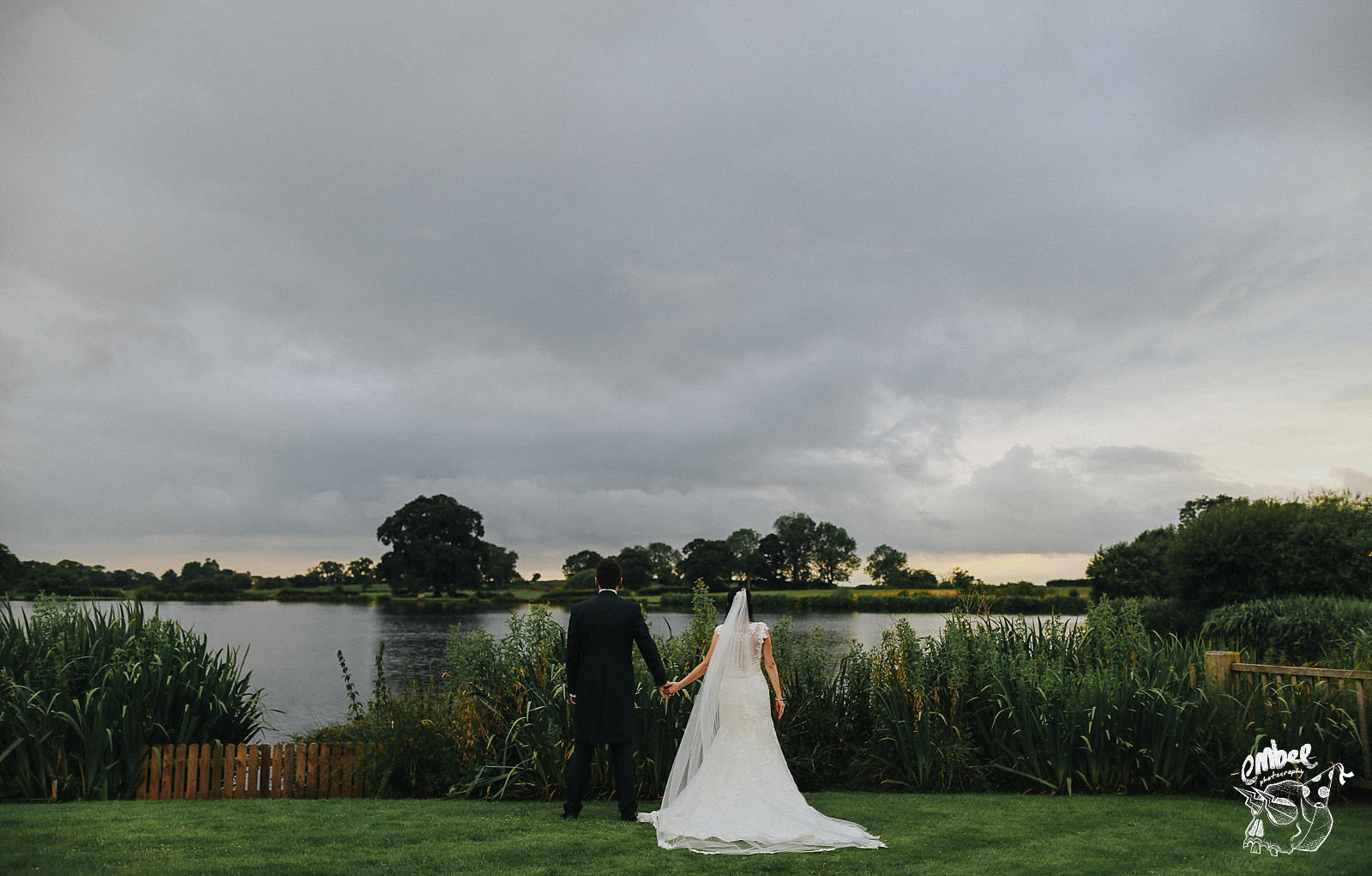 bride and groom hold hands in front of the cheshire landscape at sandhole oak barn