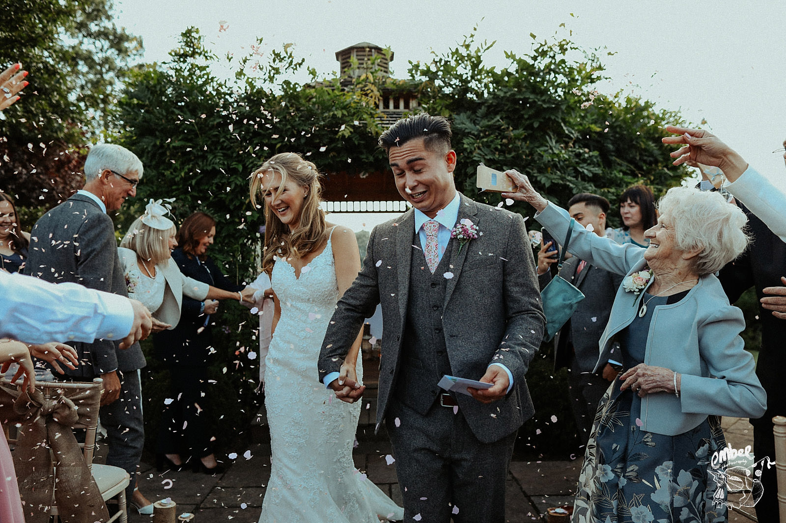 guests throw confetti all over bride and groom