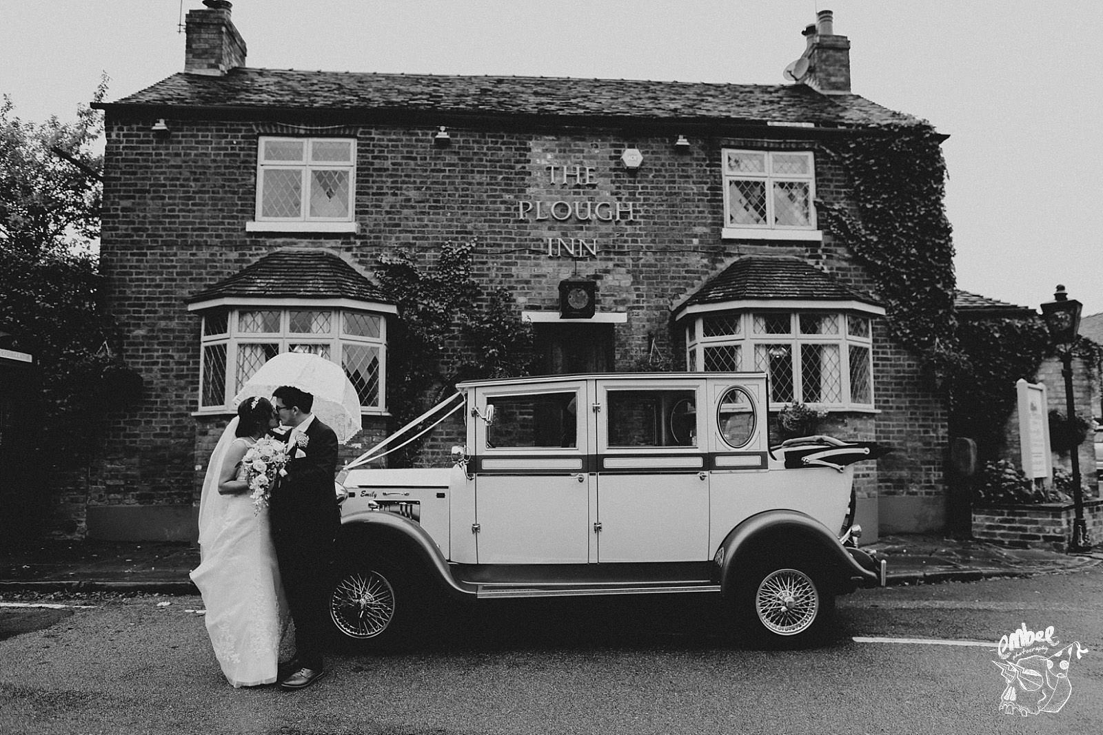 bride and groom with wedding car infant of the plough inn, eaton in cheshire