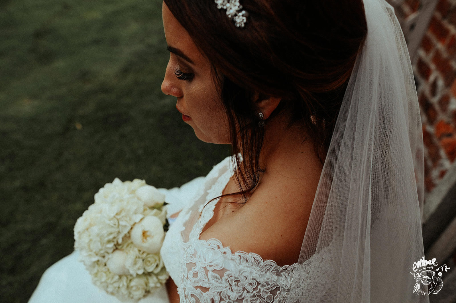 bride looking down at her flowers made of white roses