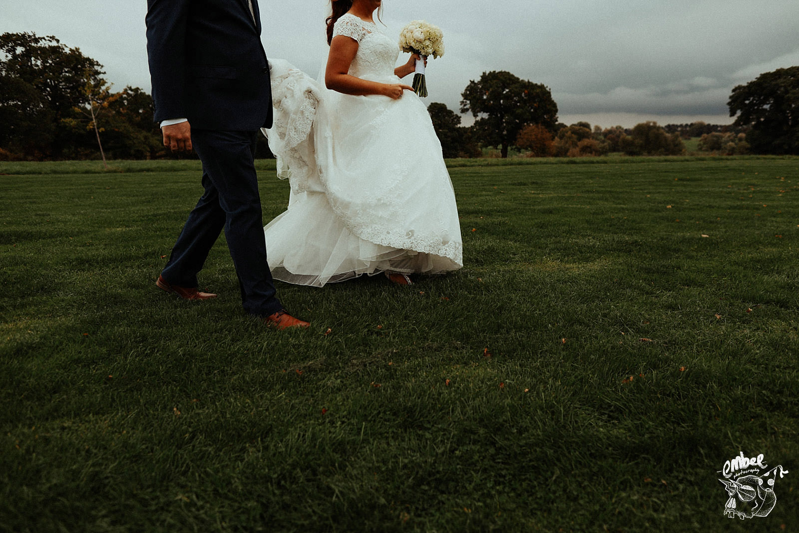 bride and groom walking in a filed