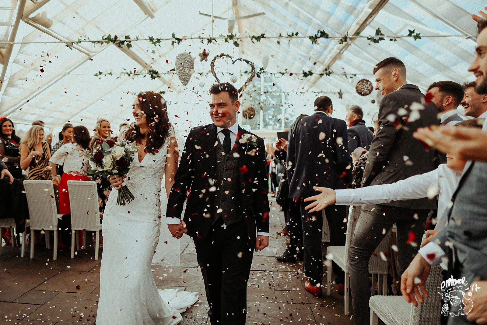 bride and groom walking down the aisle getting confetti thrown on them