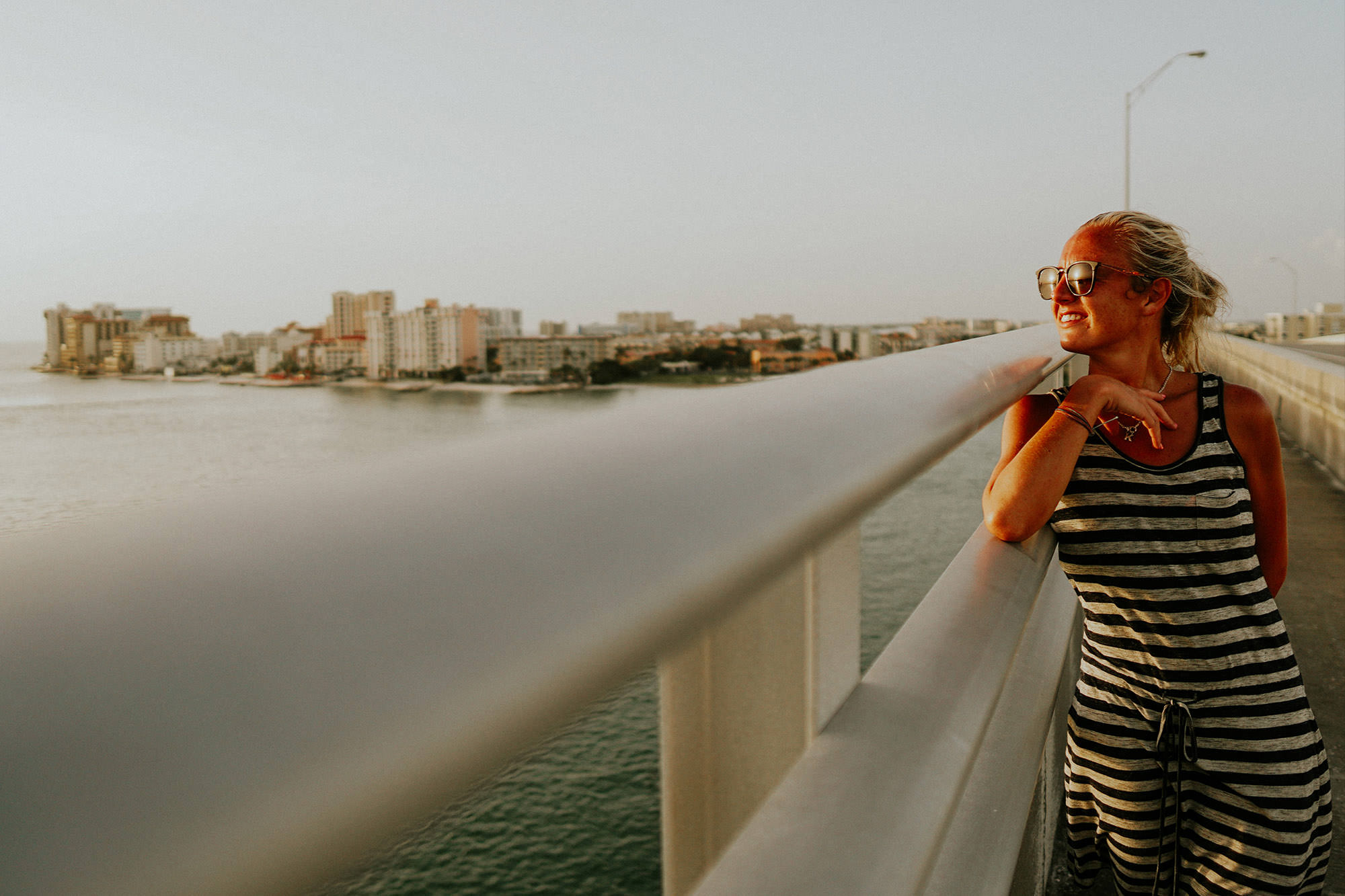 girl with shades on looking into the sunset on a bridge in clearwater