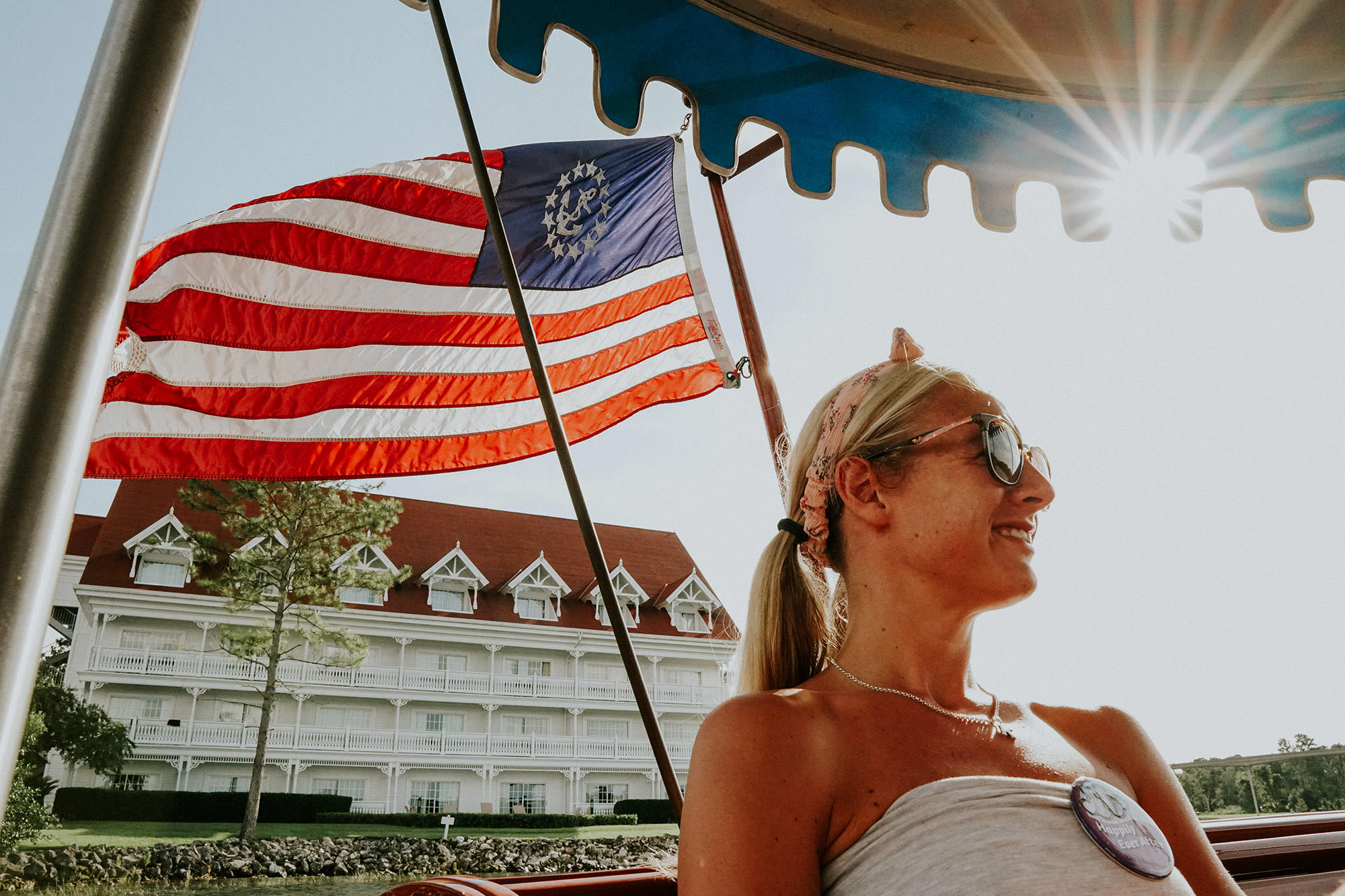girl in sunshine with american flag behind her in disney