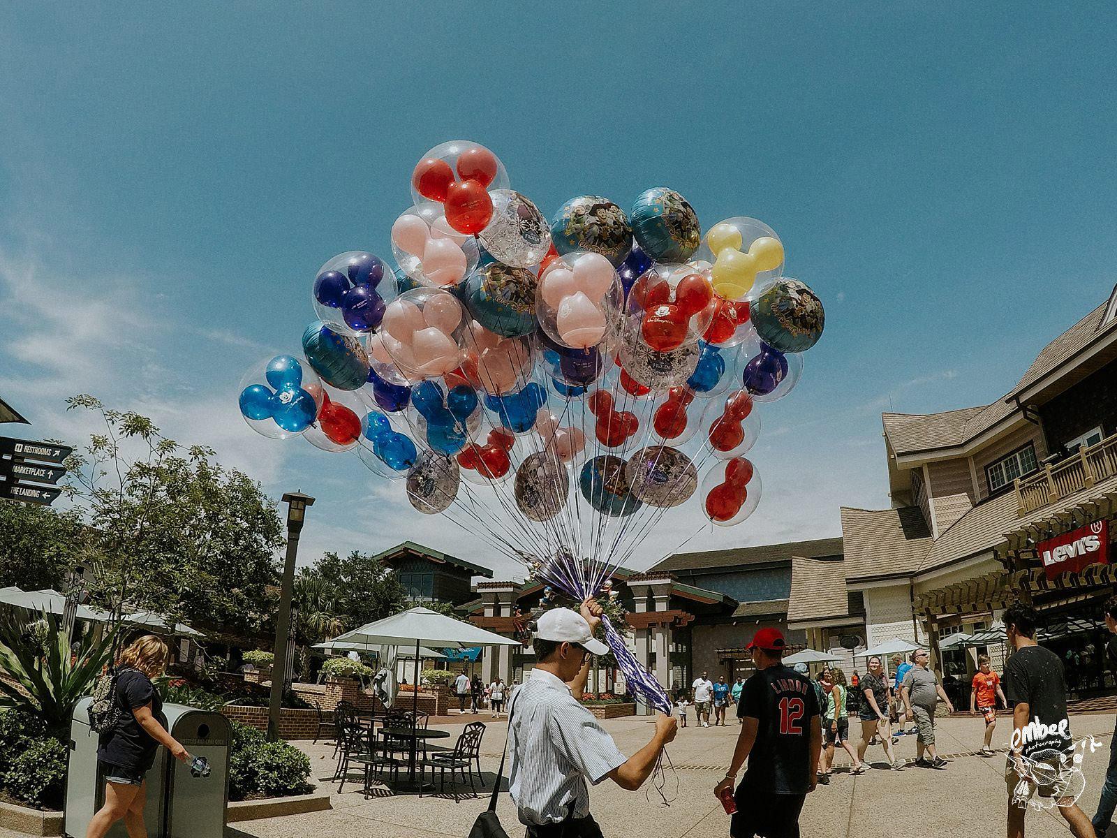 man holding disney balloons