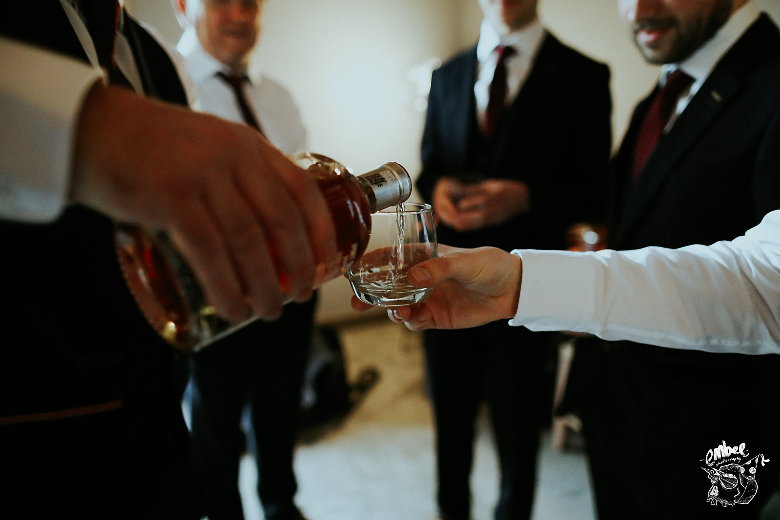 groom pouring whisky into a glass