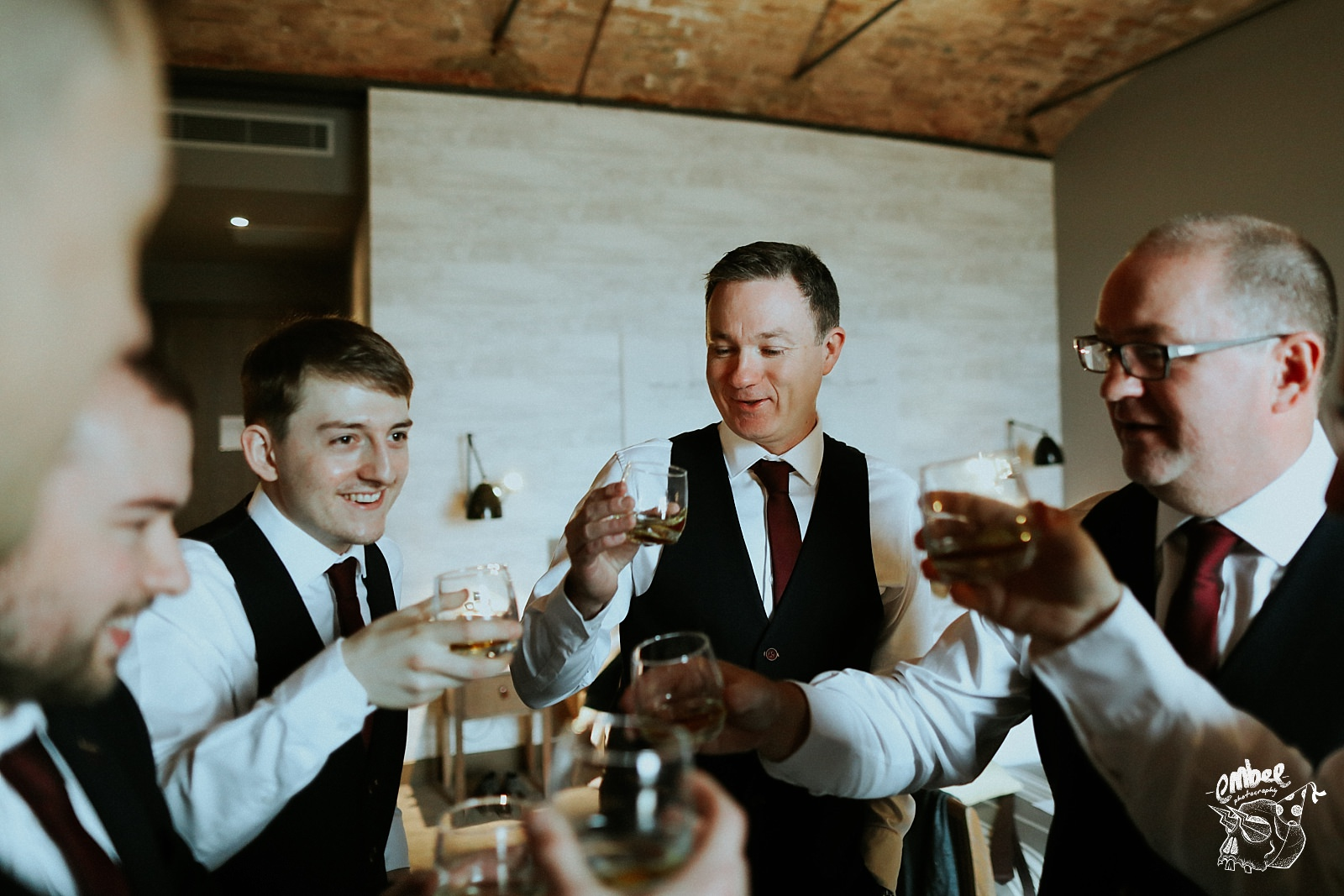 groom cheers with wedding party and whisky