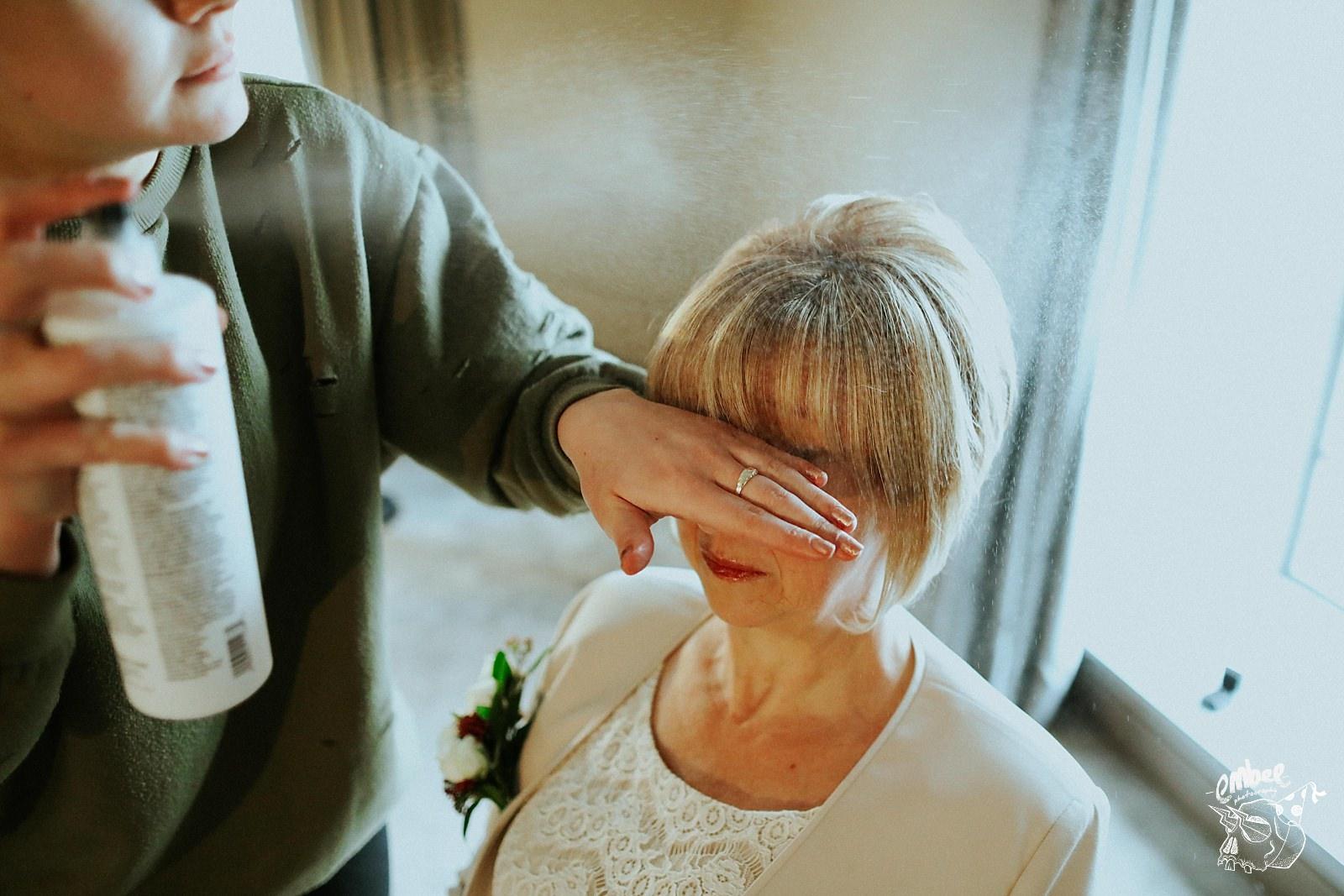 spraying hairspray on womans hair