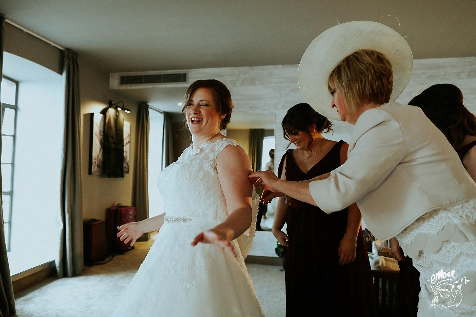 mum helping bride button up her dress