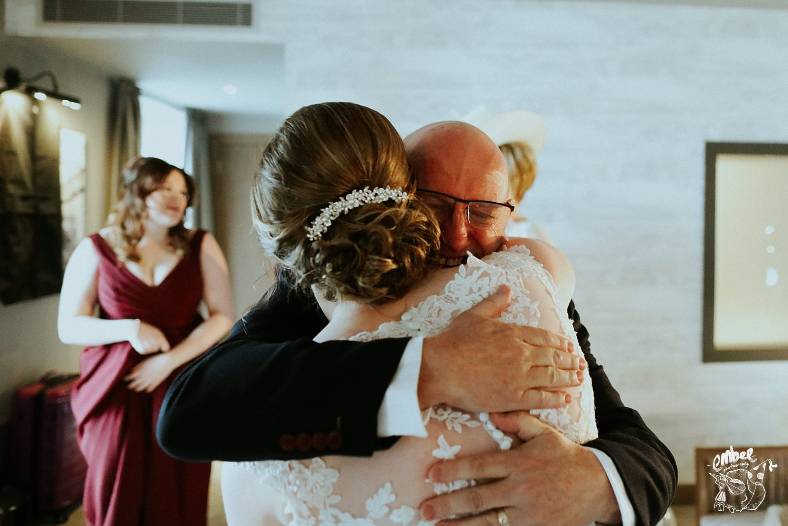 father of the bride crying and hugging his daughter
