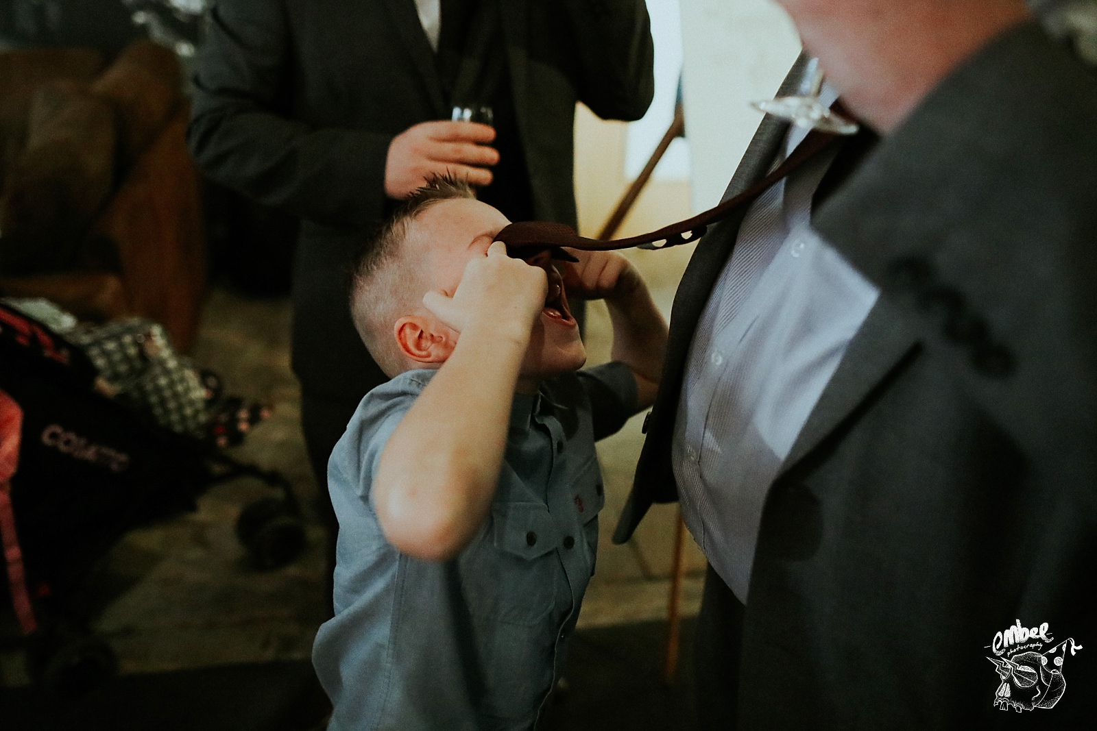 kid playing with mans tie