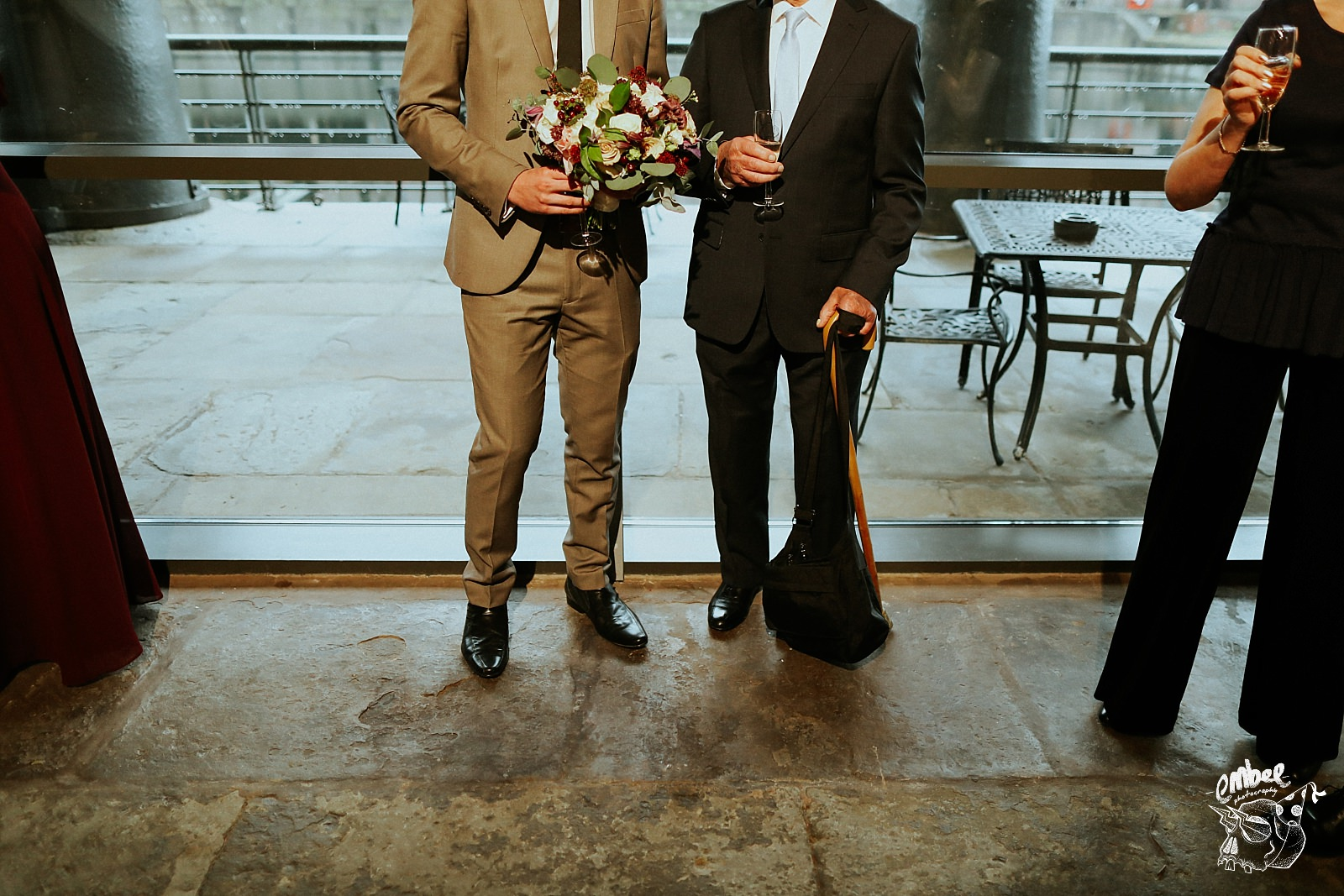 lower profile of two wedding guest, one is holding flowers